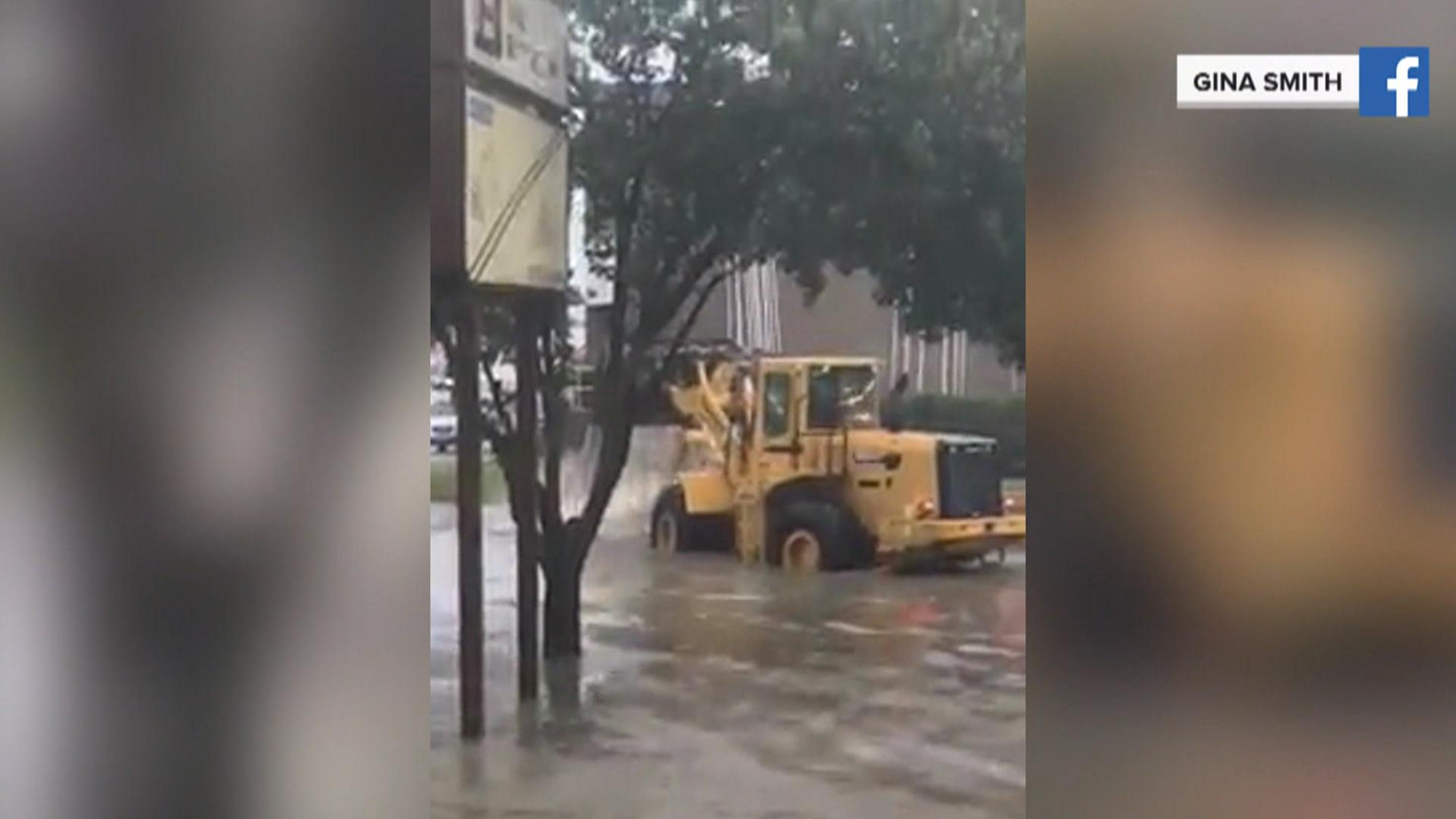Front-end loader douses car that caught fire in Texas flood