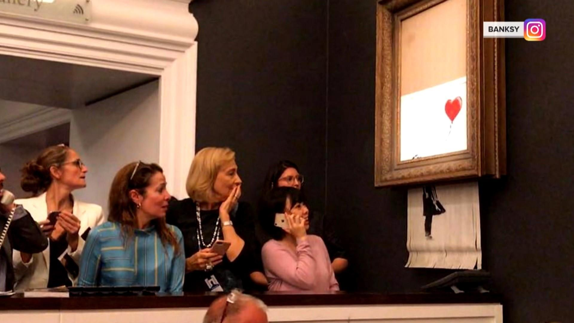 Banksy painting shreds itself moments after being sold for $1.4 million at London auction