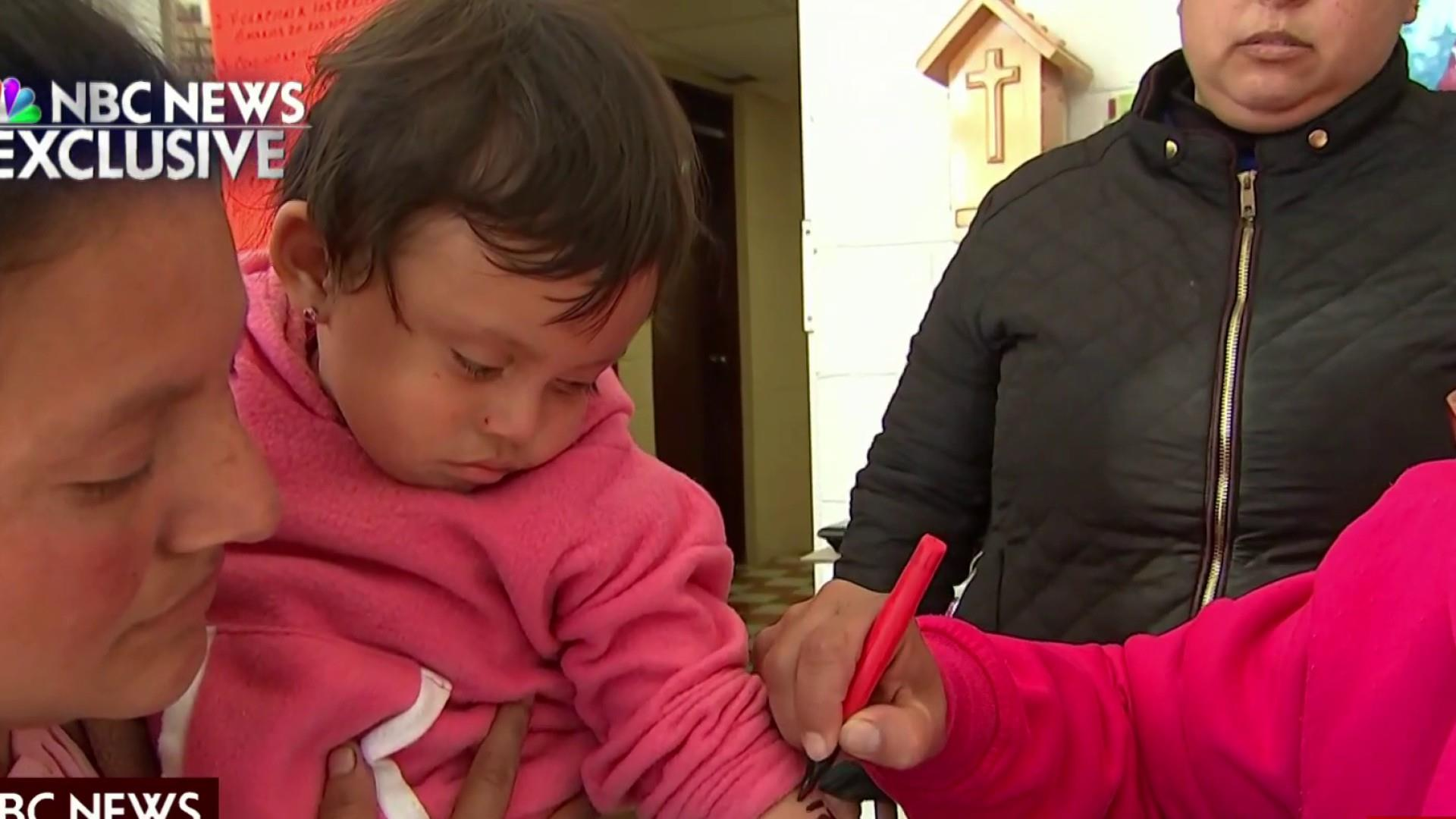 Migrant children with numbers on arms wait to cross border