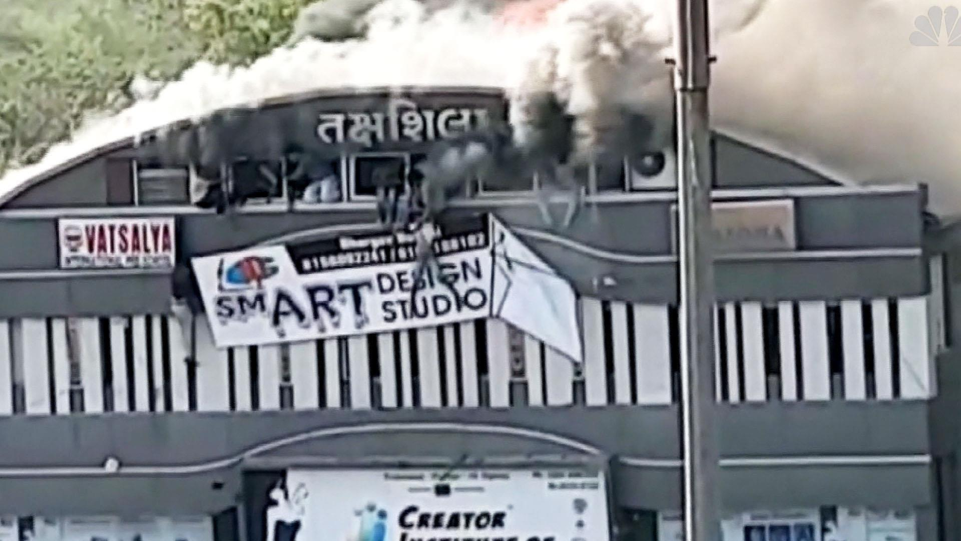 Students plunge from top floor of burning building in Surat, India