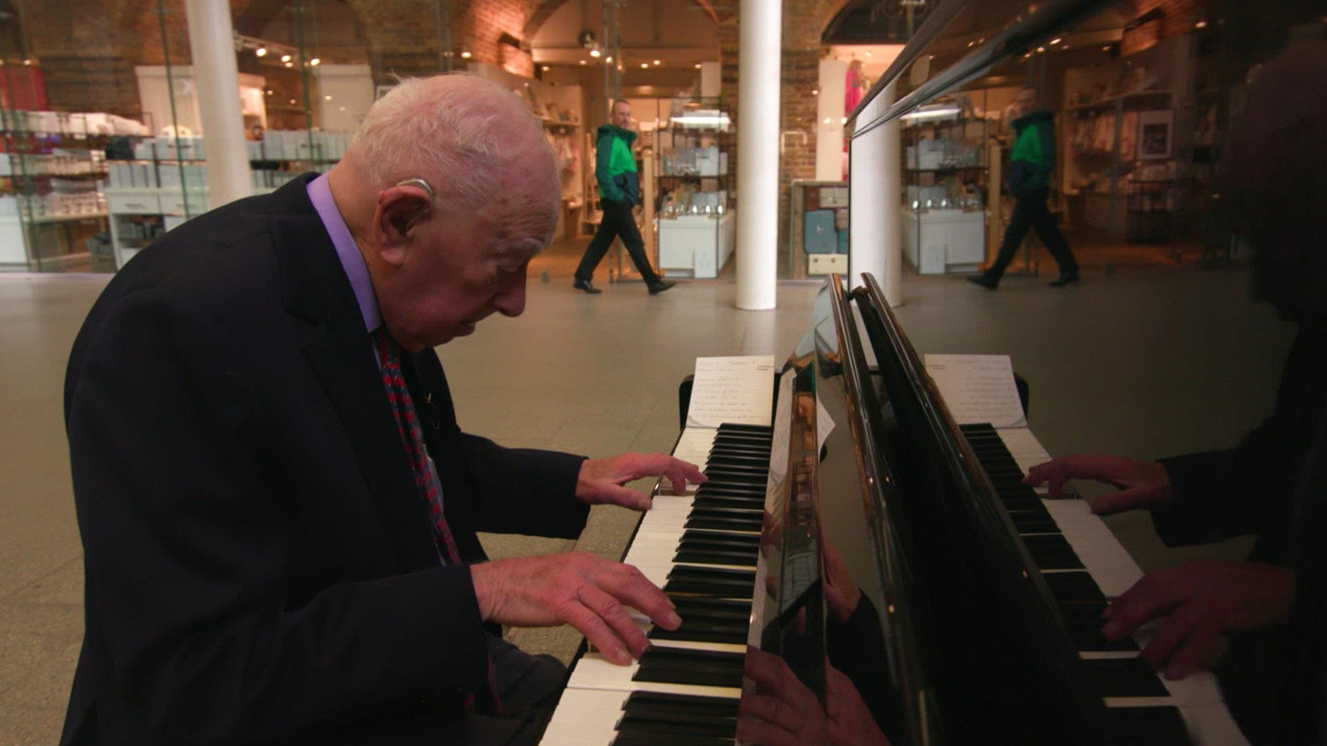Denis Robinson, 91, entertains travelers on a street piano at London's St. Pancras station