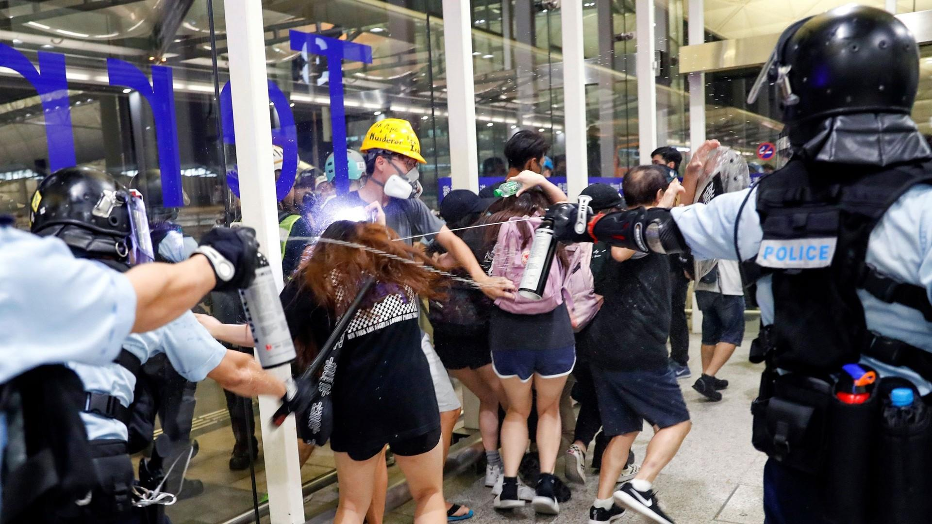Riot police clash with protesters at Hong Kong airport as demonstrations grow violent