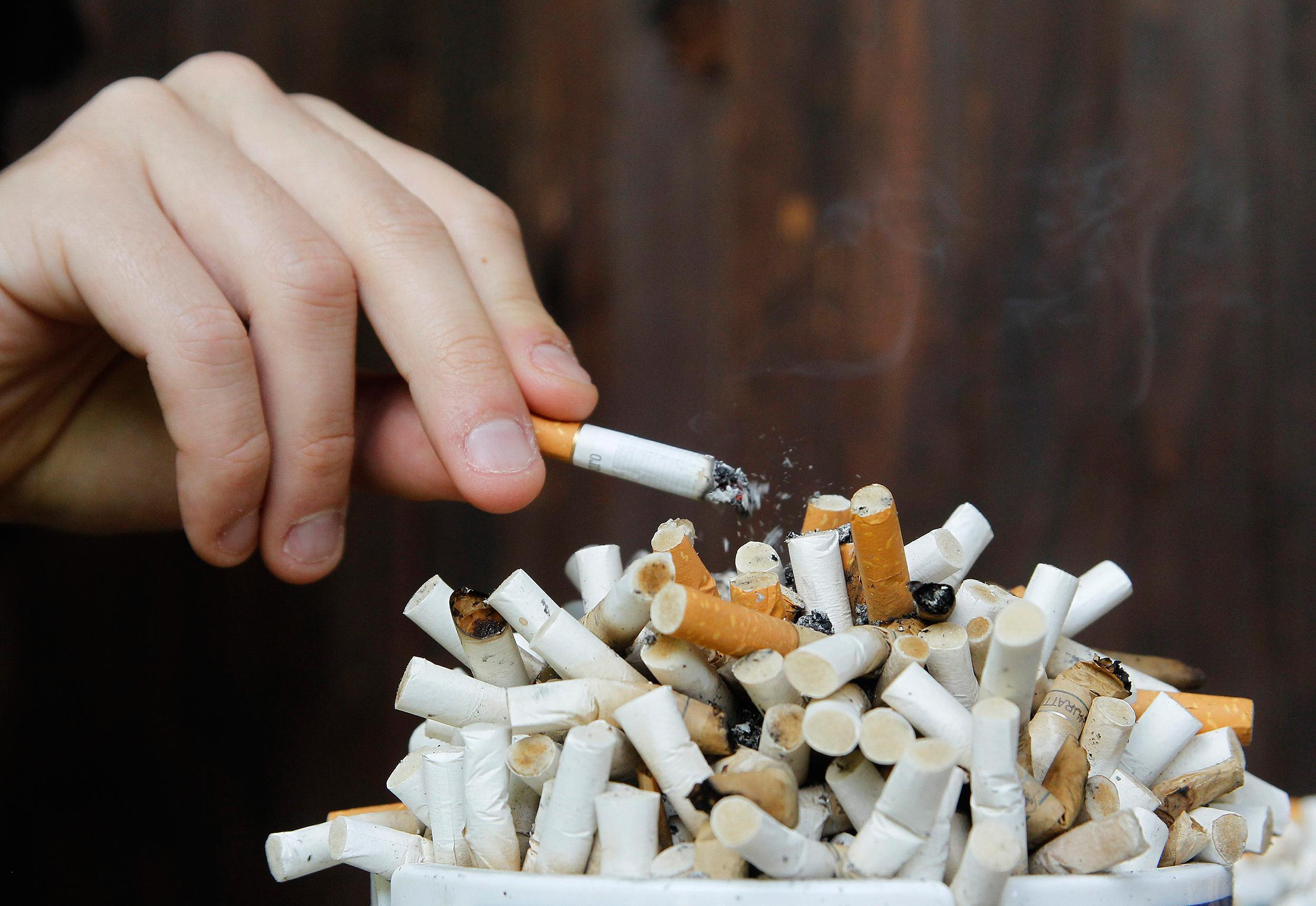 Image: A man taps ashes off his cigarette into an ashtray filled with cigarette butts on a table.