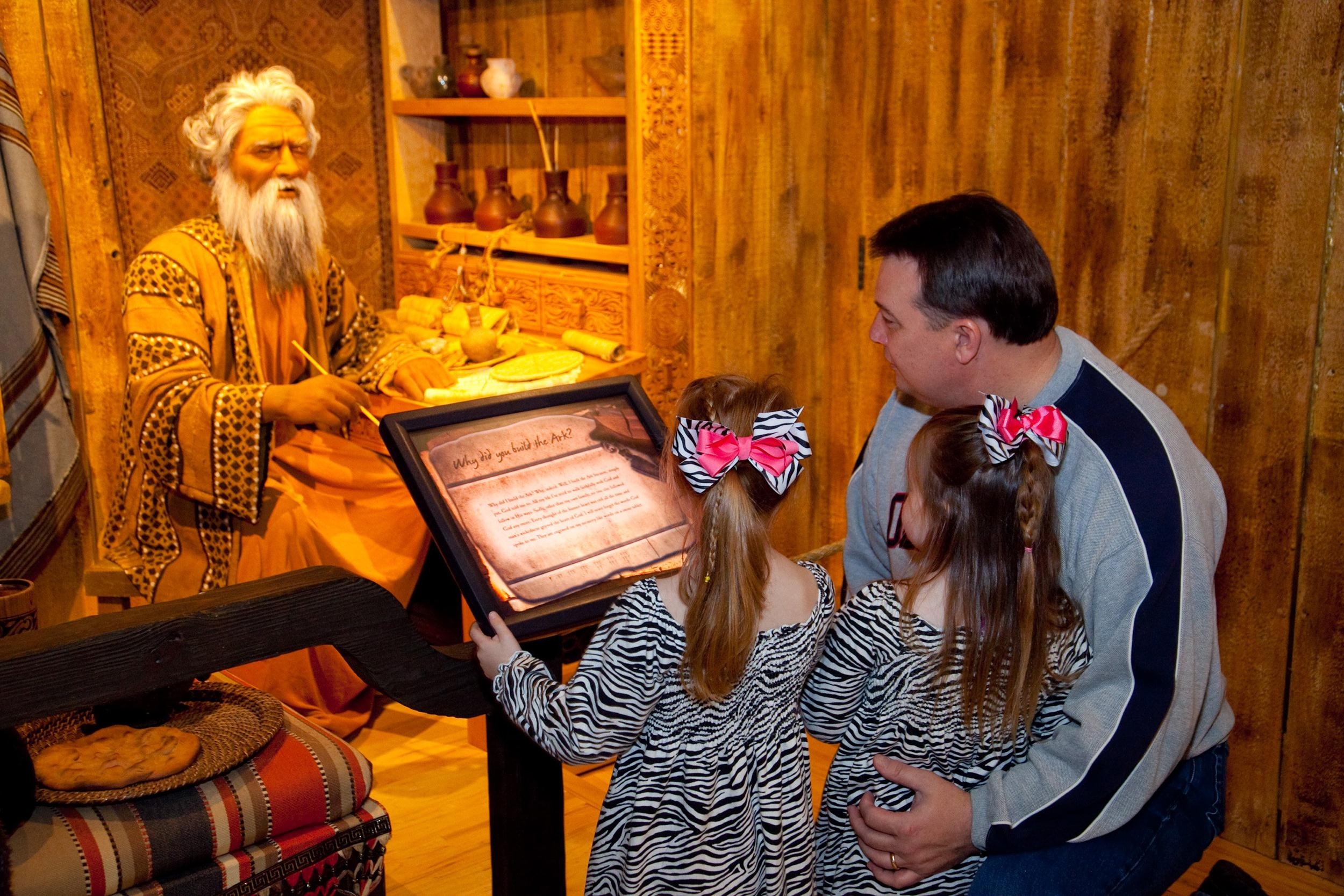 Image:  Sisters Bella, 5 and Laura Katherine Coker 3, of Jackson, Miss tour the Creation Museum in Petersburg, Ky with their father John Coker. One of the animatronic displays allows visitors to ask question of Noah including one