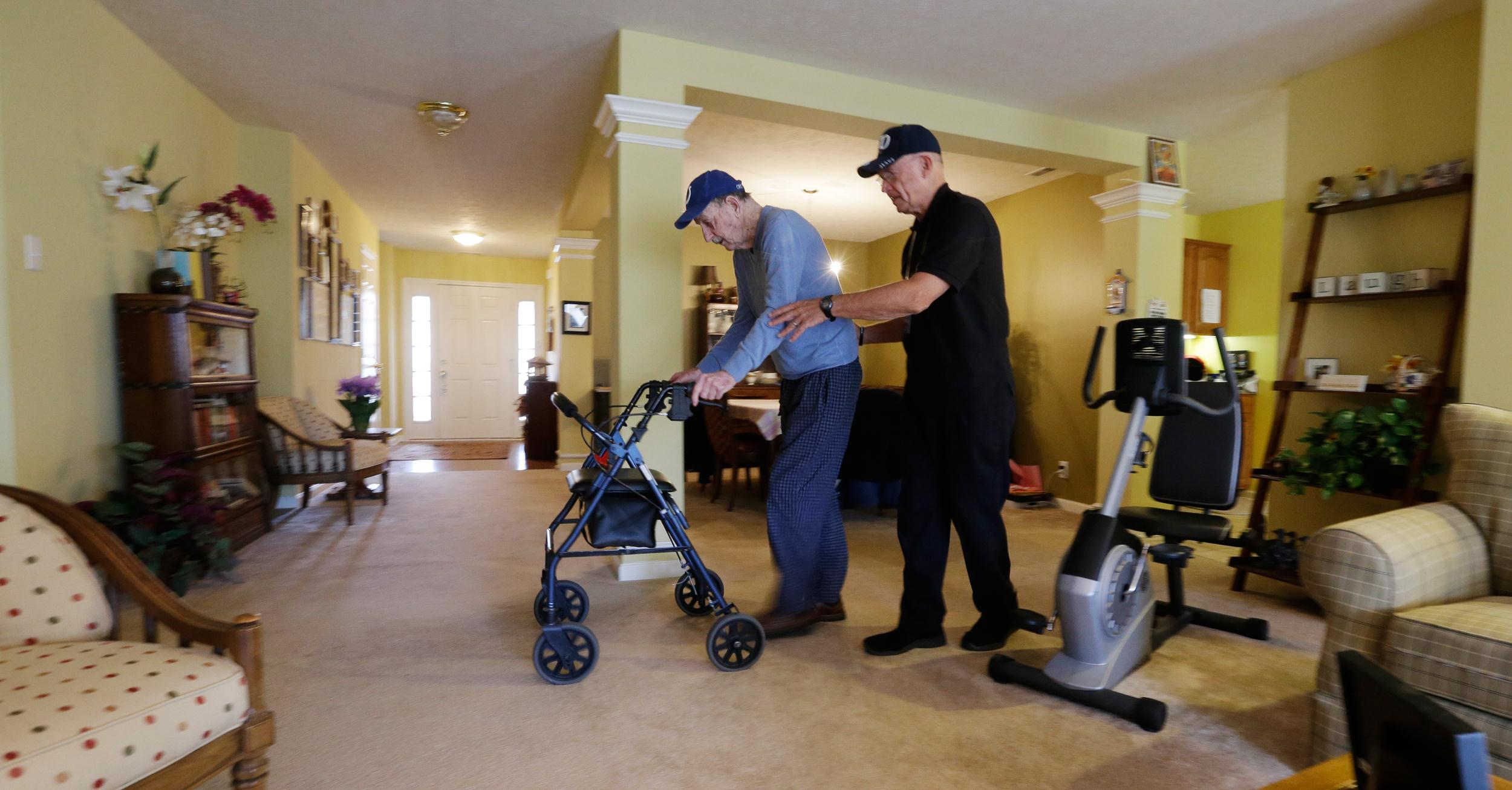 Image: Caregiver Warren Manchess, right, walks across the living room with Paul Gregoline, 92, in Noblesville, Ind. on Nov. 27, 2013.