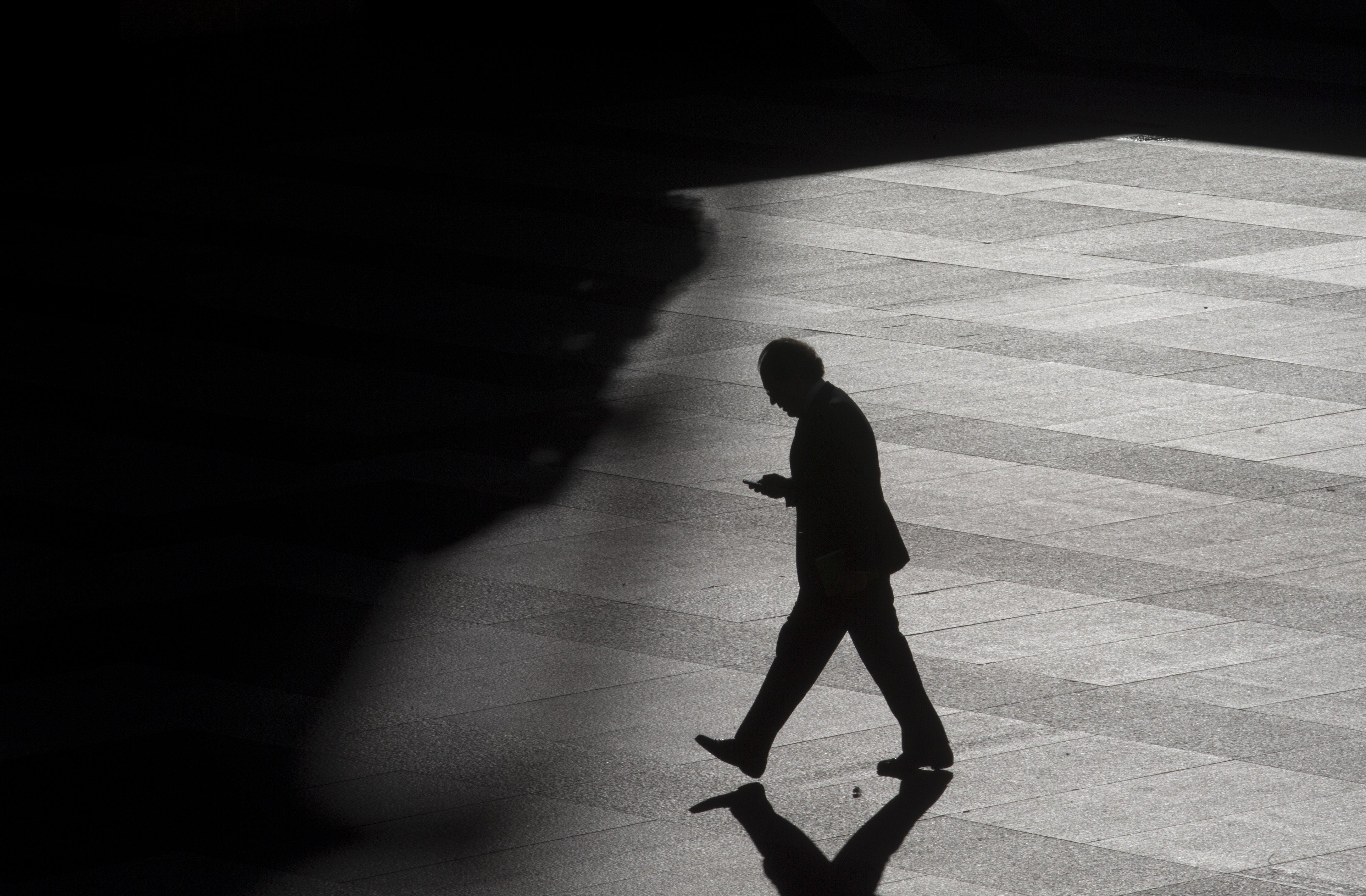 Image: A man looks as his cell phone as he walks into the shadows.