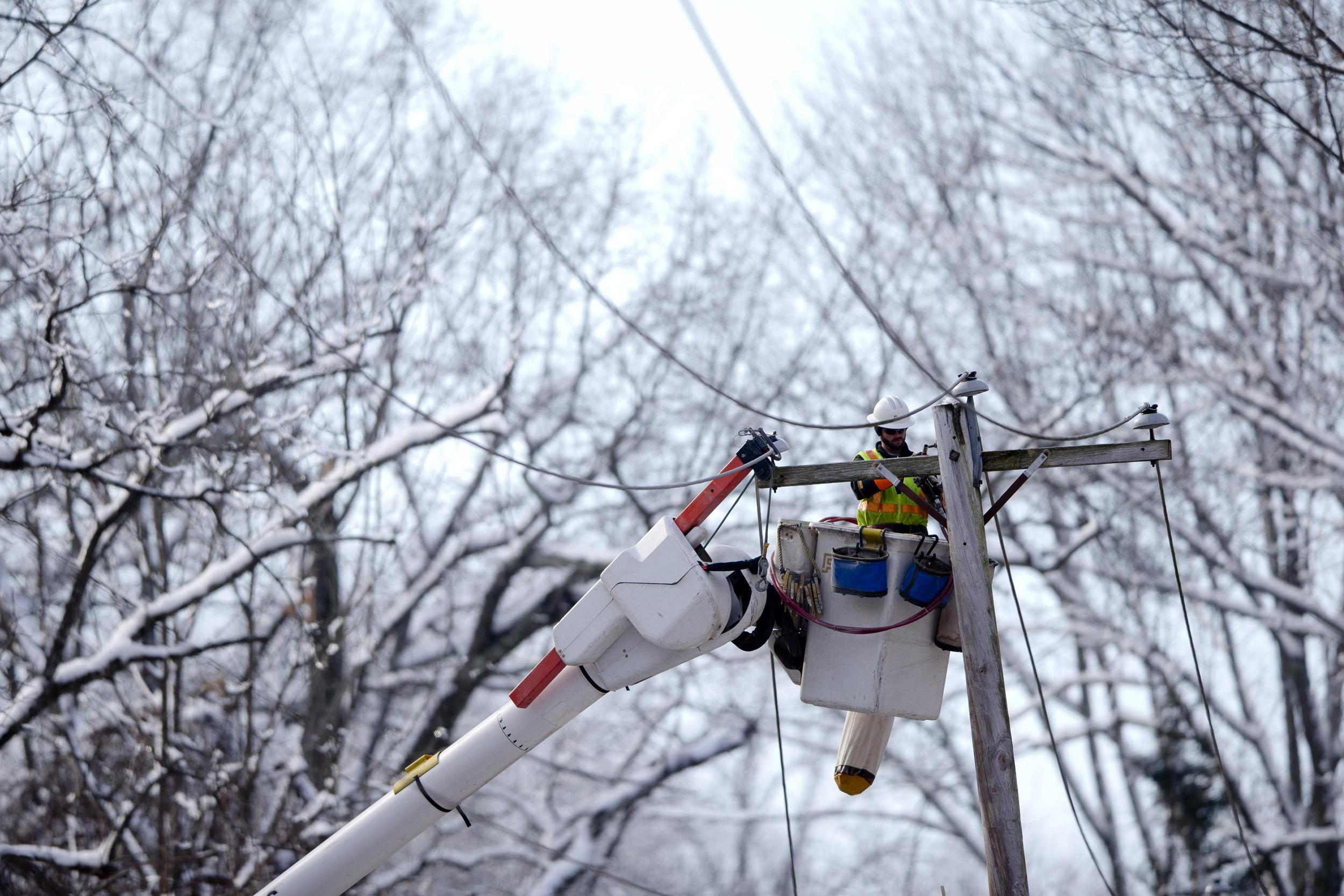 Image: A linesman works to restore electrical power in Downingtown, Pa.