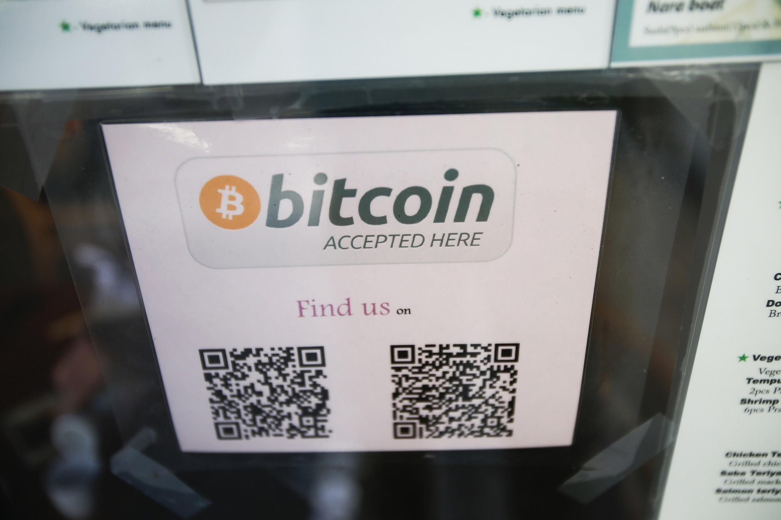 A Bitcoin logo is seen at the window of Nara Sushi, a restaurant that accepts Bitcoin.