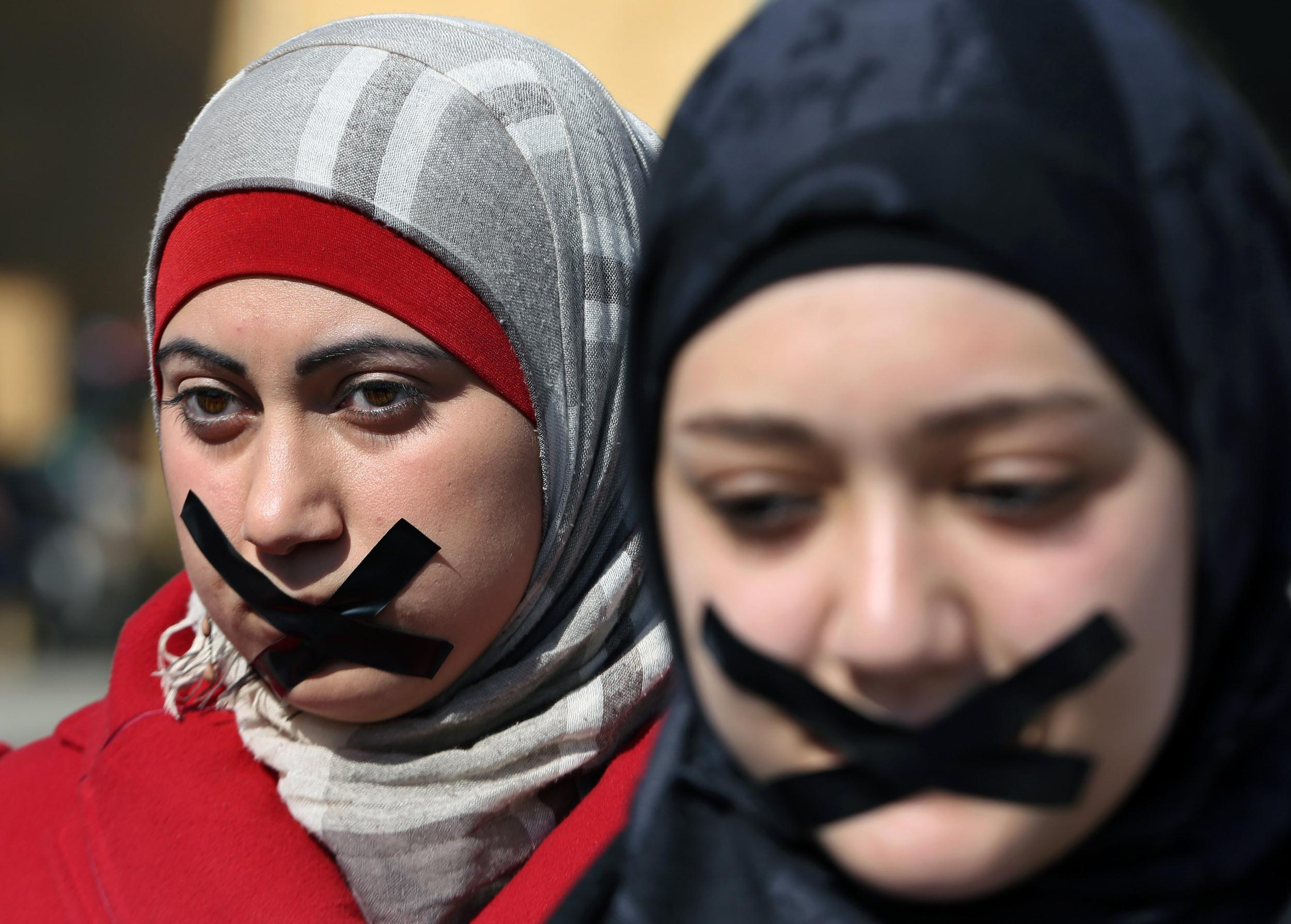 Image: Lebanese journalists and activists use tape to cover their mouths to show their solidarity with detained journalists in Egypt