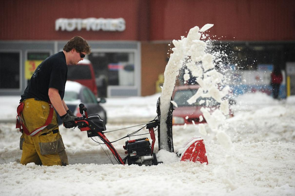Image: Matthew Cunningham uses a snow blower to clear the sidewalk.