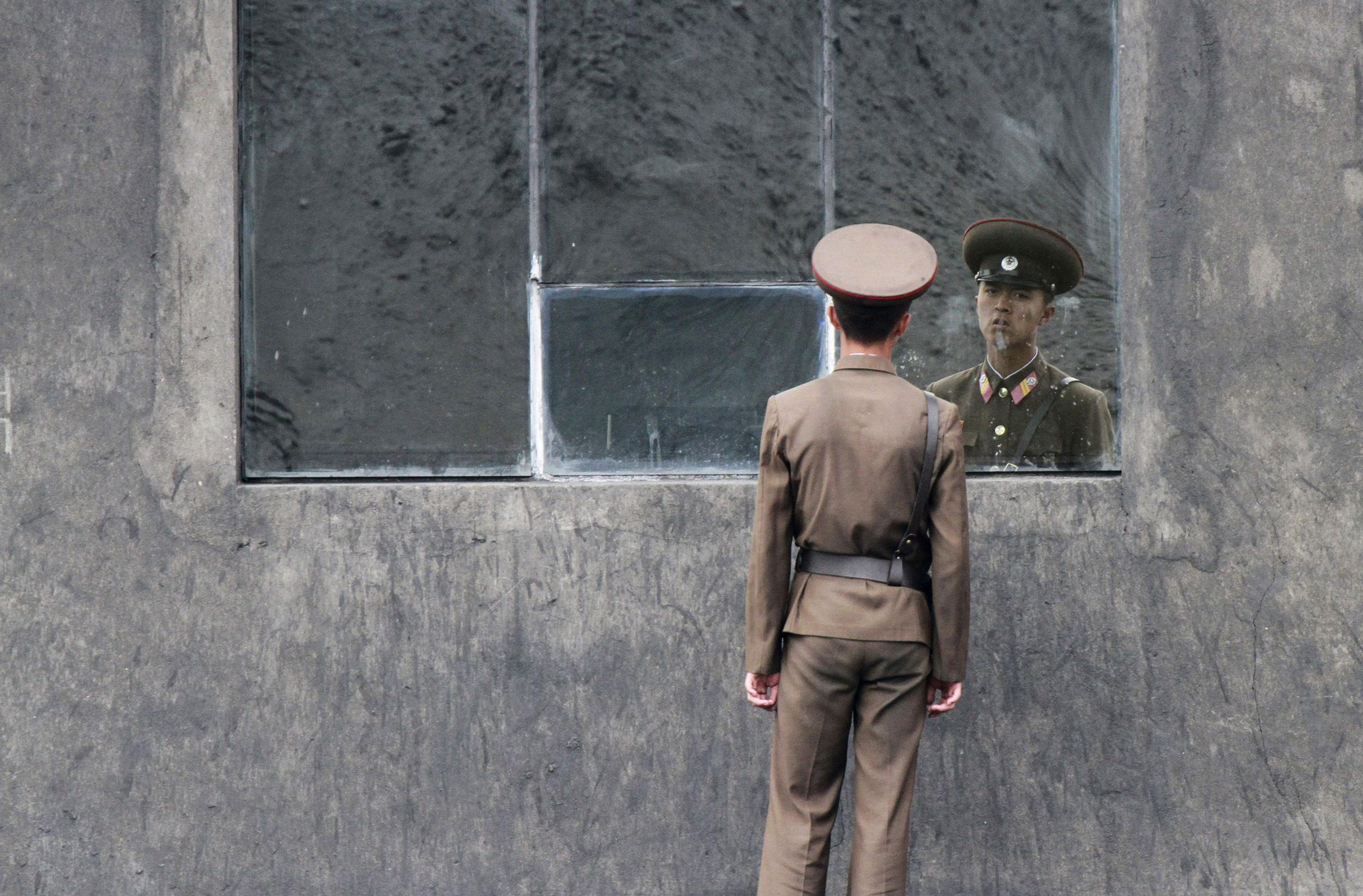 Image: A North Korean soldier stands in front of a window.