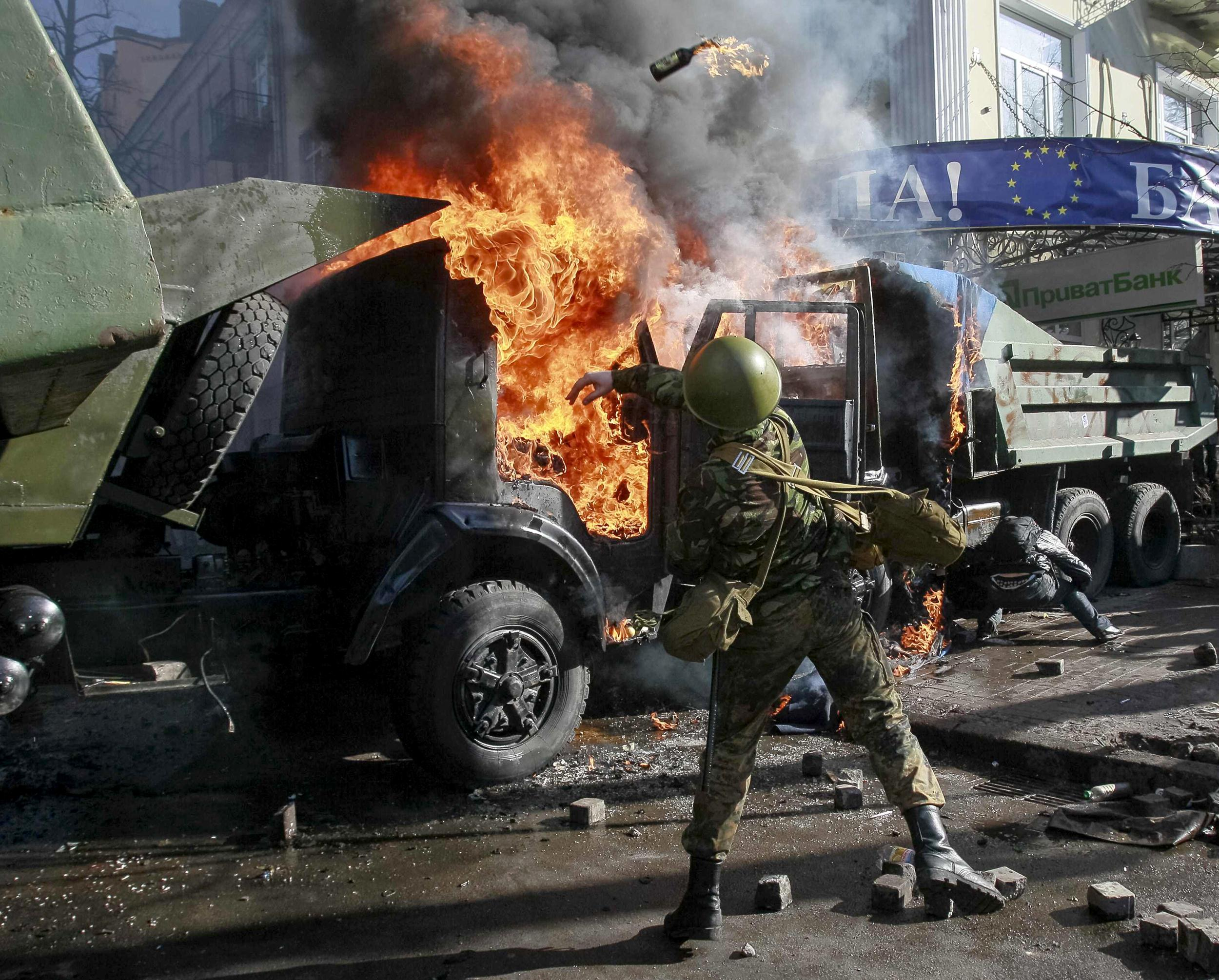 Image: An anti-government protester throws a Molotov cocktail in Kiev