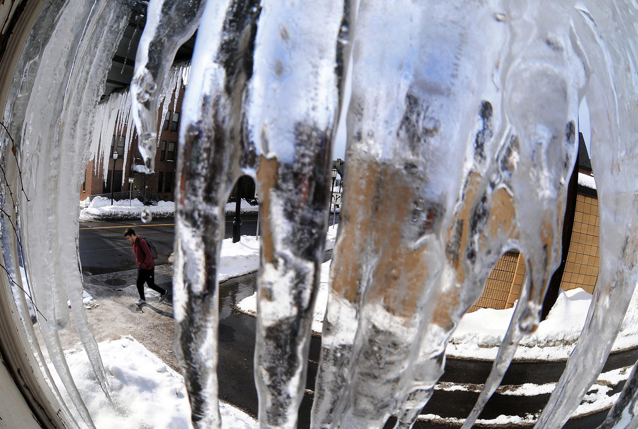 Image: A pedestrian passes near a cluster of slowly melting icicle's in downtown Scranton, Pa.