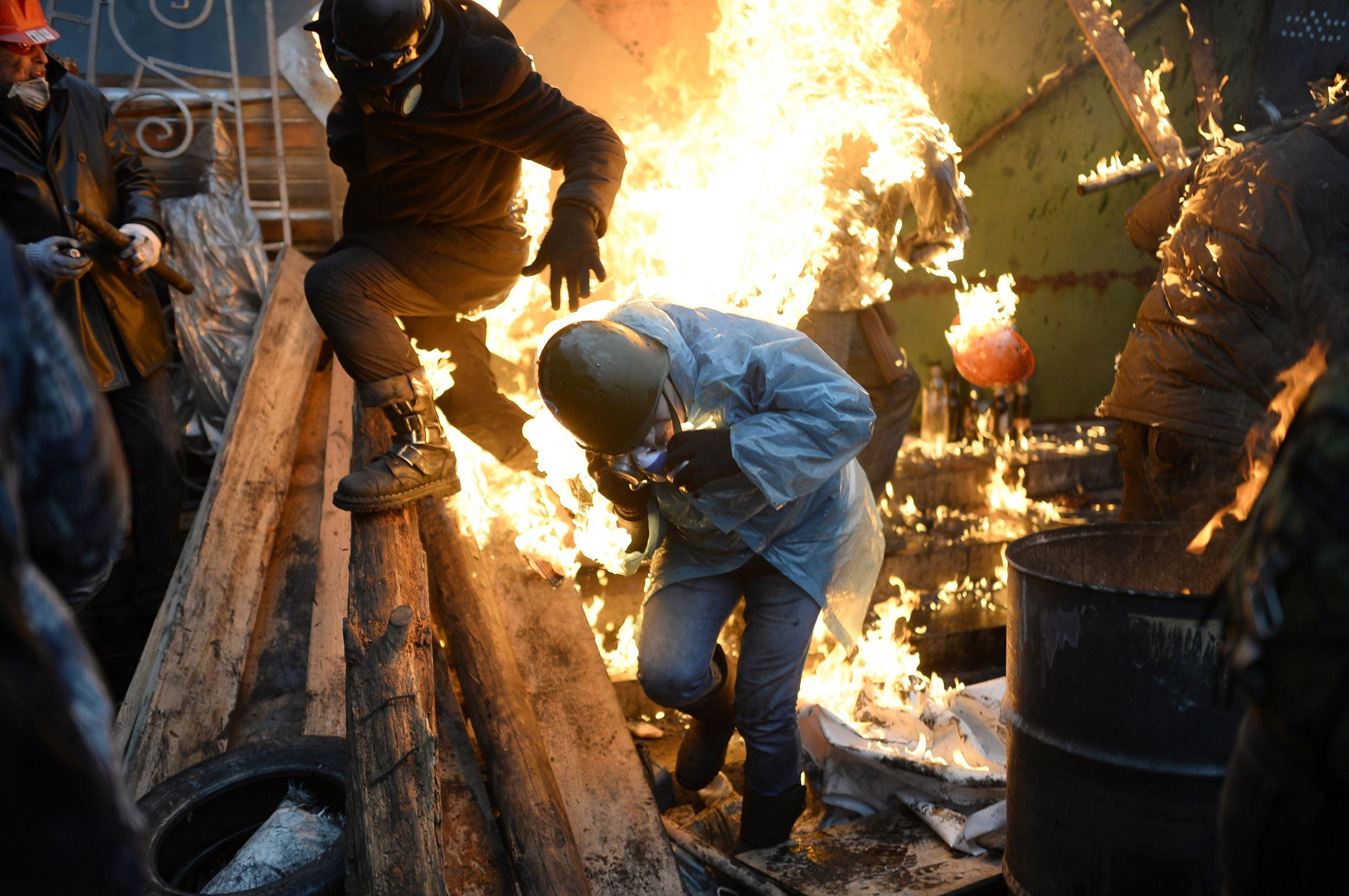 Image: Protesters try to protect themselves from fire as they stand behind burning barricades during clashes with police