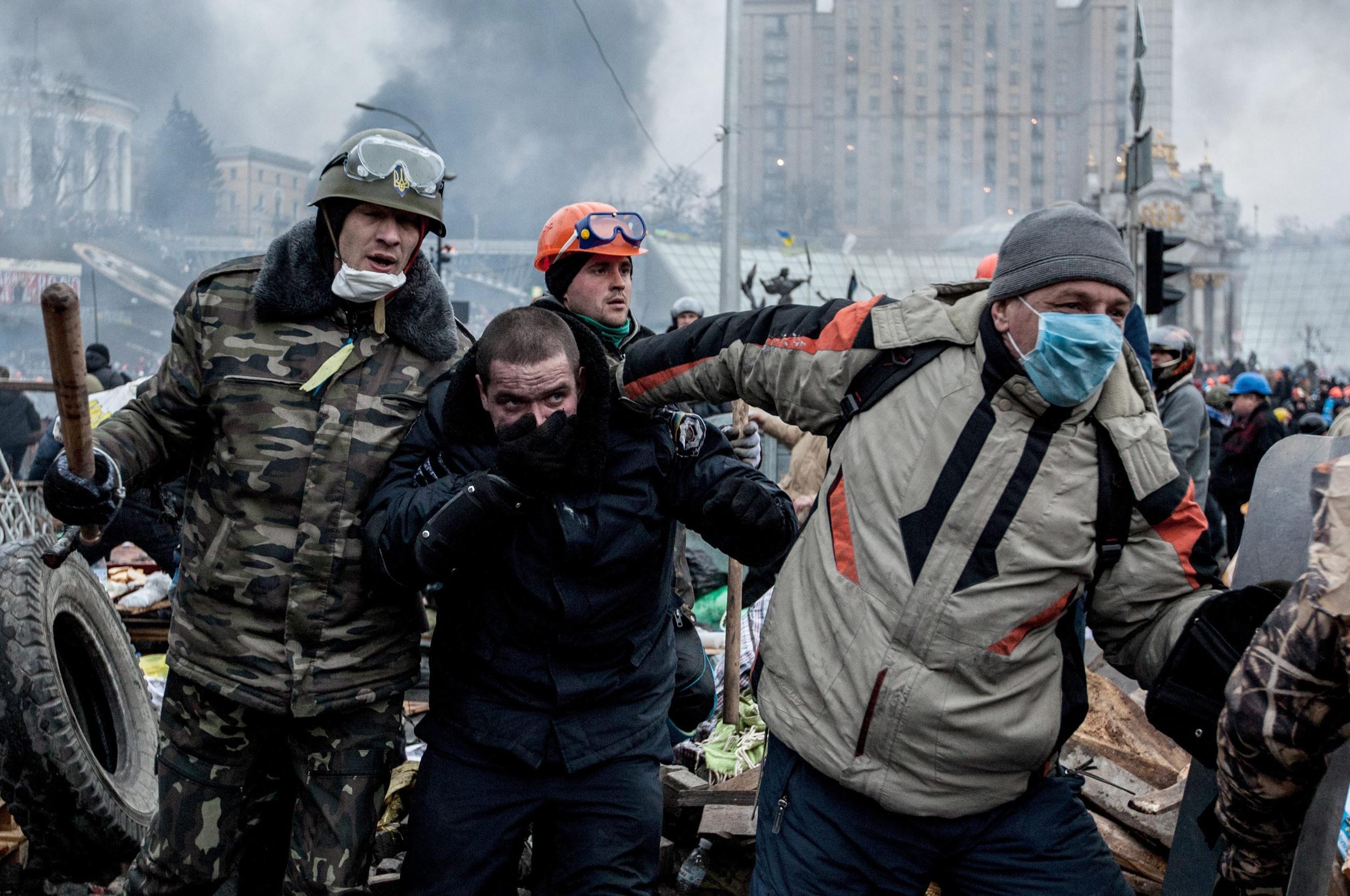Image: Anti-government demonstrators escort a captured police officer in Kiev