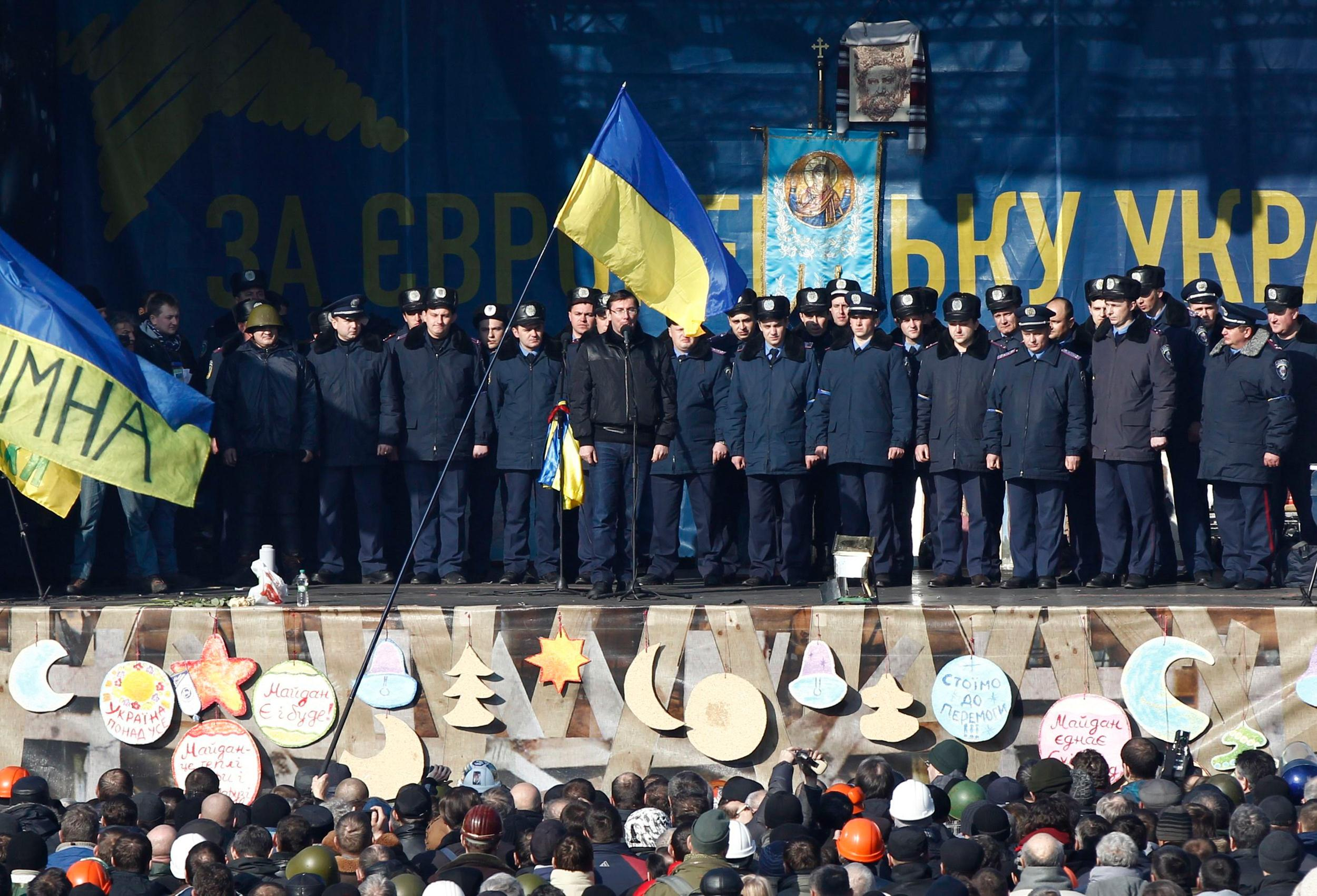 Image: Police officers from Lviv who have arrived to join anti-government protesters appear on a stage in Independence Square in Kiev