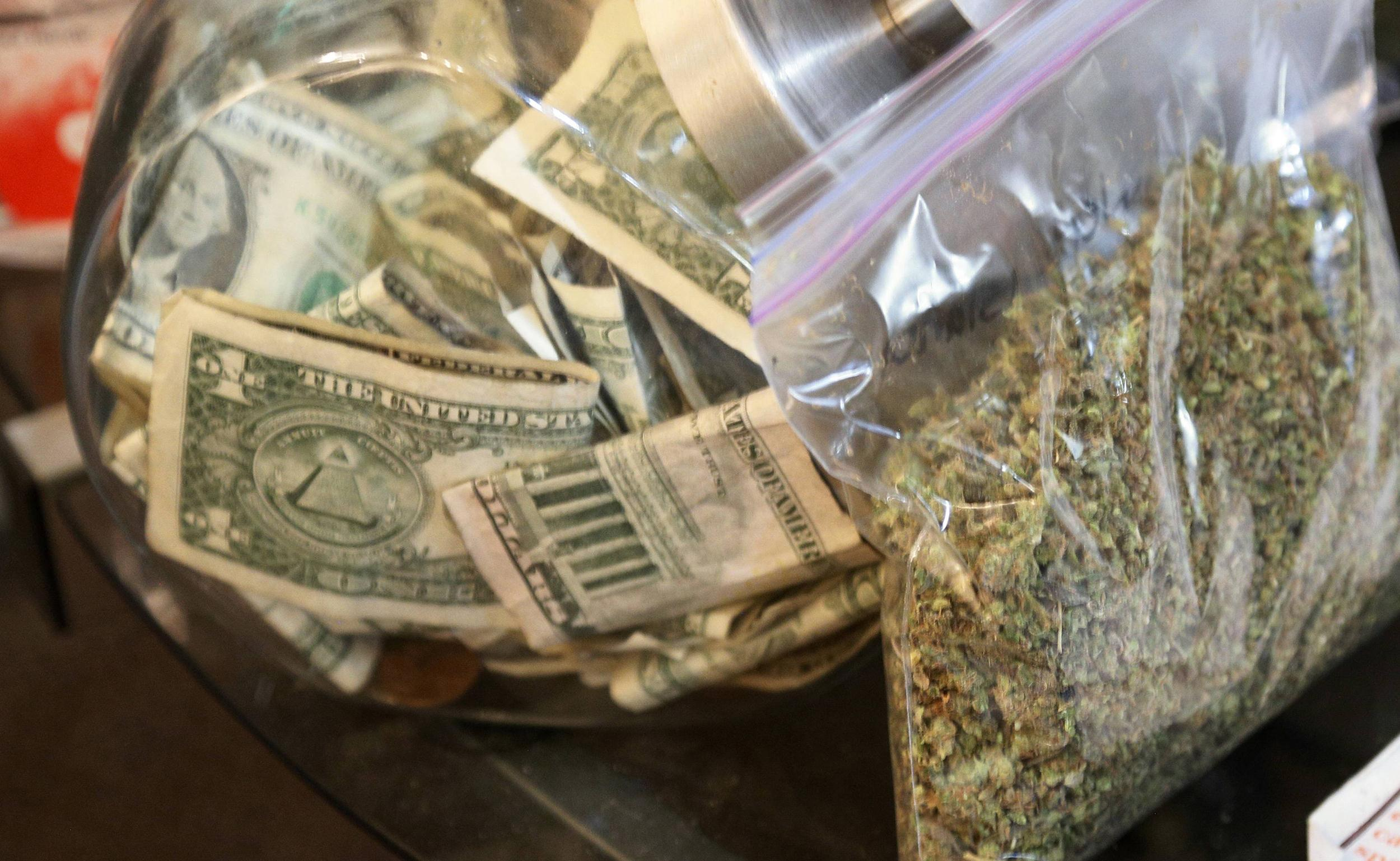 Image: A bag of marijuana being prepared for sale sits next to a money jar at BotanaCare in Northglenn, Colorado