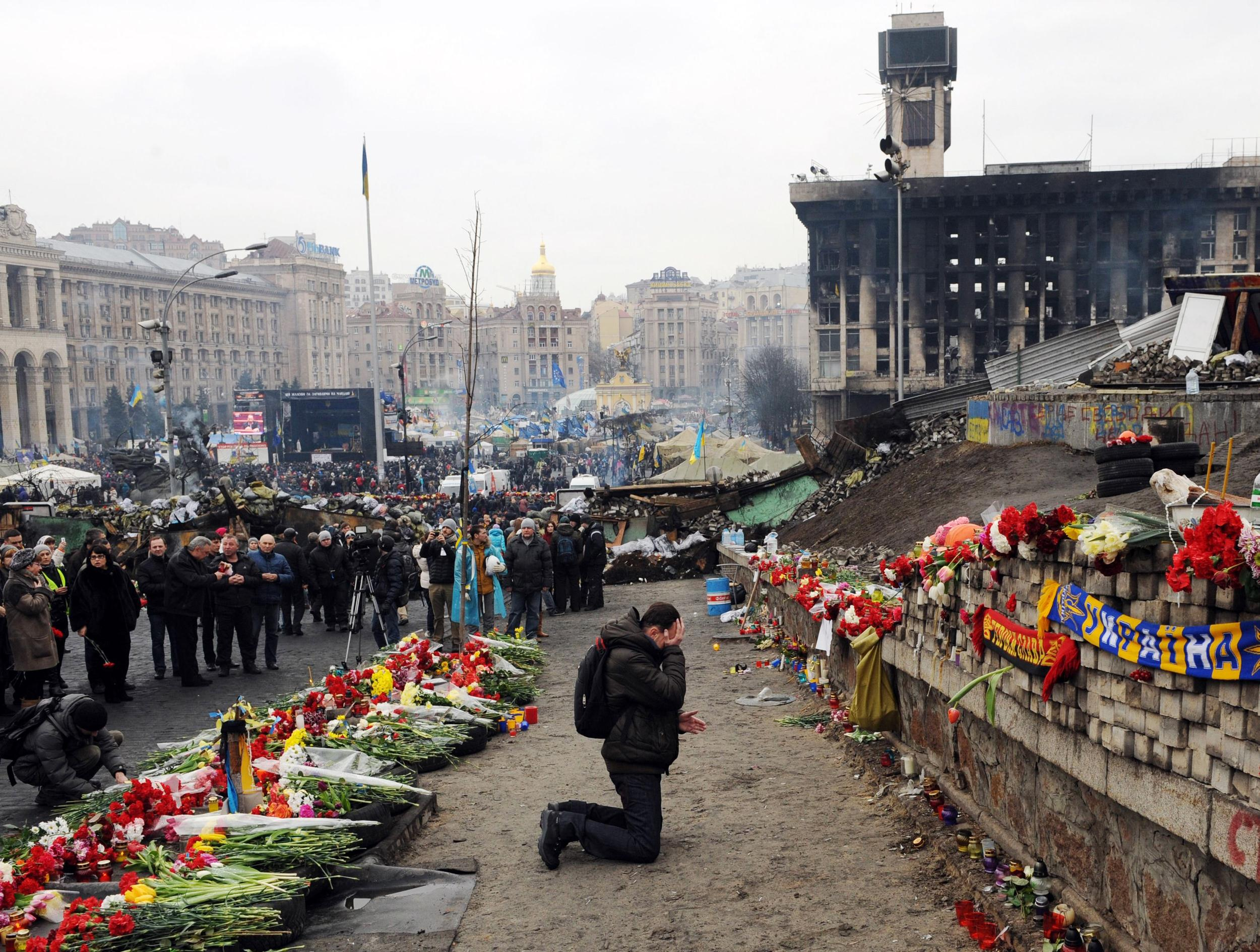 Image: A man cries at a memorial to the anti-government protesters killed in the past weeks clashes with riot police on Kiev's Independence Square on February 23, 2014.