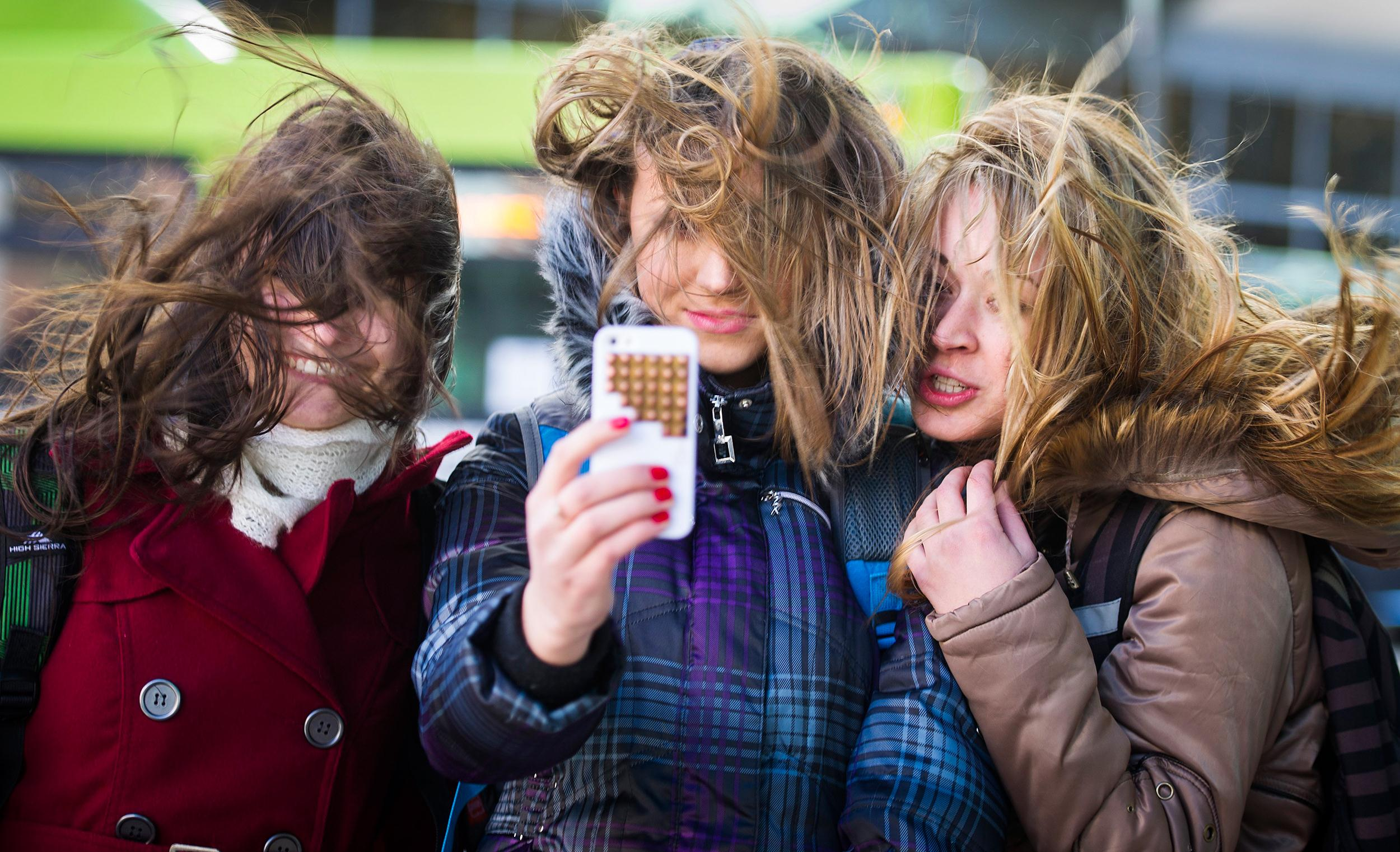 Image: Three young women take a group selfie of their hair flying in the wind