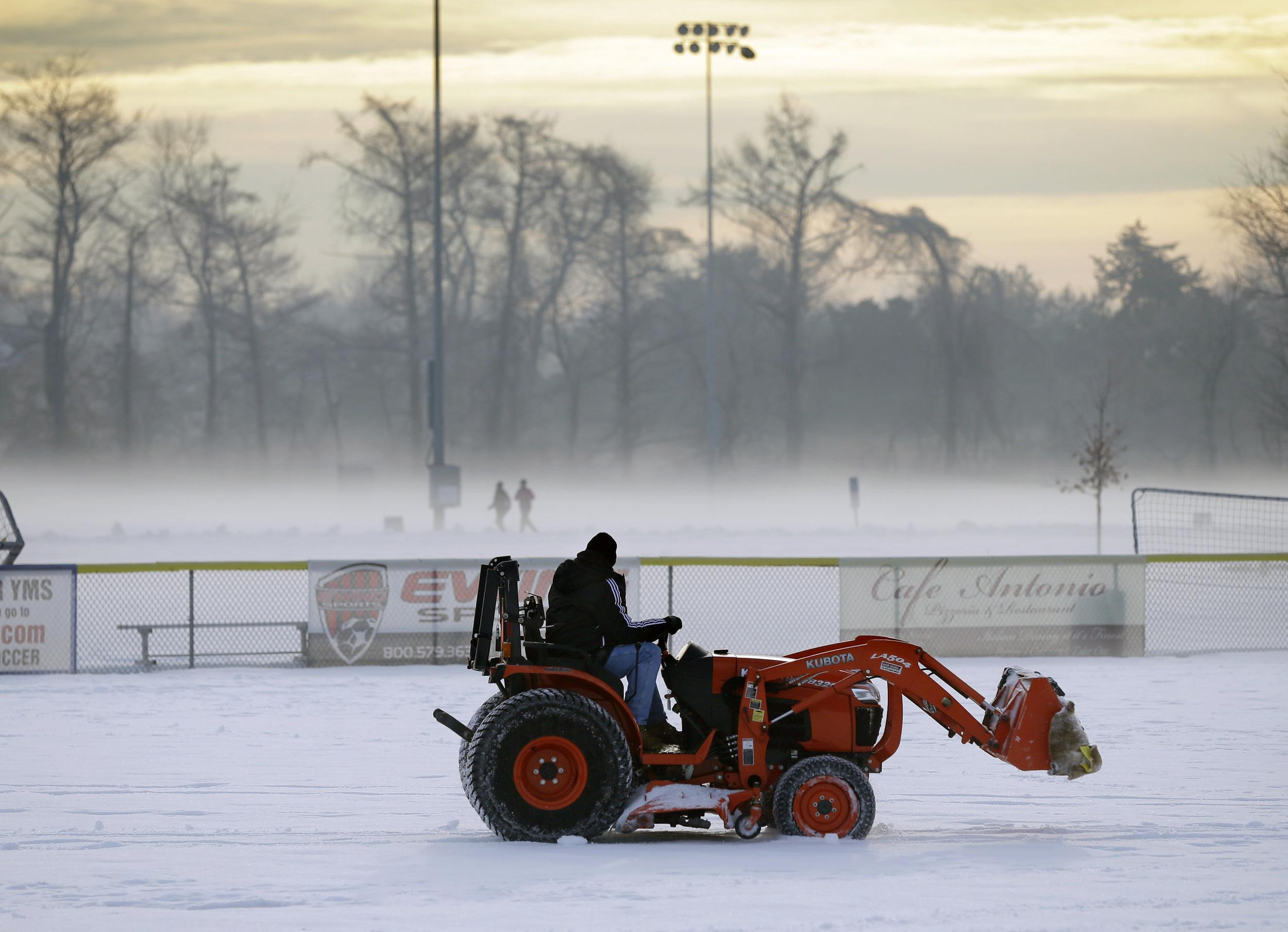 Image: Tractor clears snow from soccer field in Yardley, Pa., on Saturday
