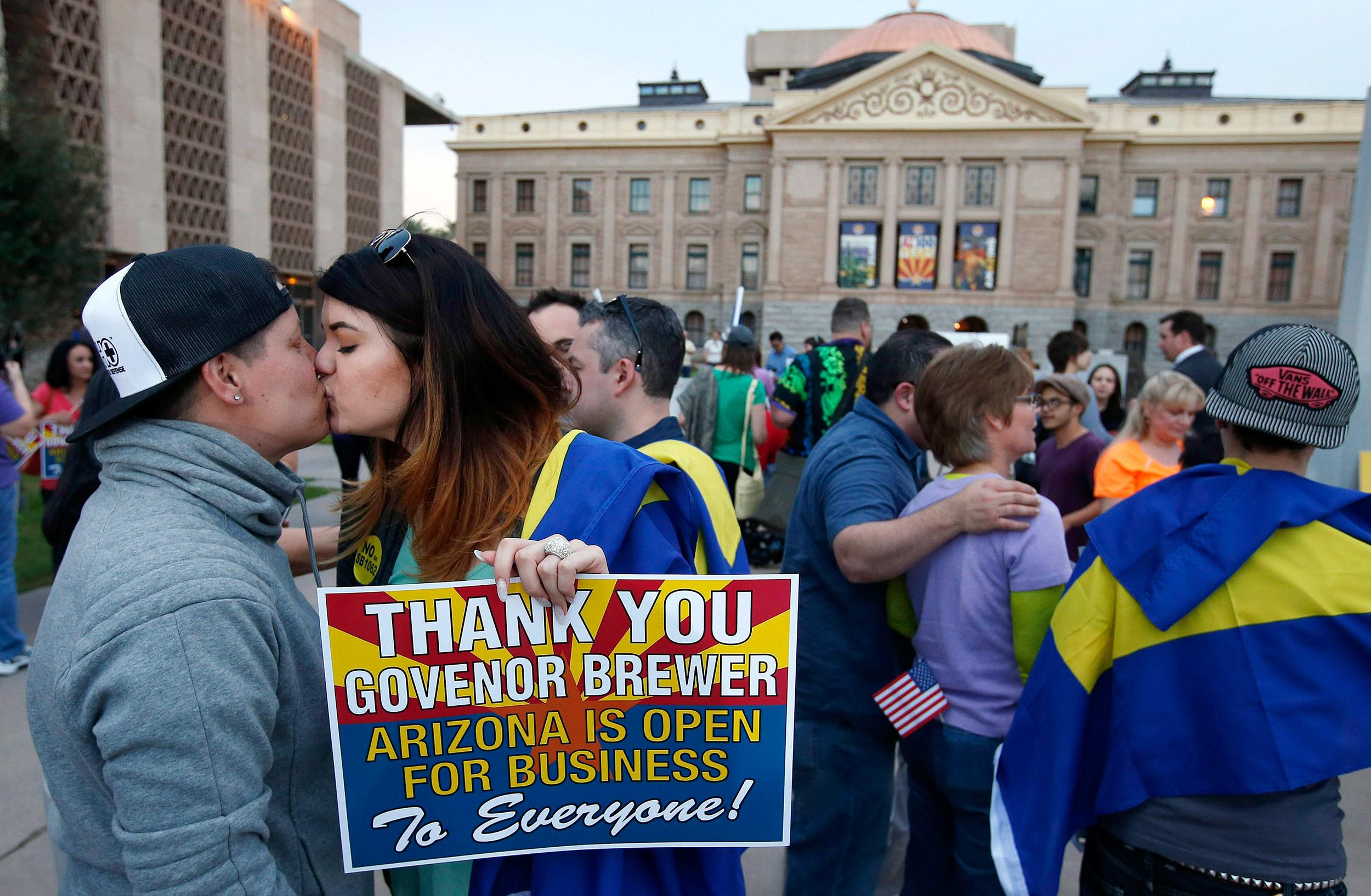 Image: With the Arizona Capitol in the background, gay rights supporters kiss after the two learn that Arizona Gov. Jan Brewer announces she has vetoed SB1062