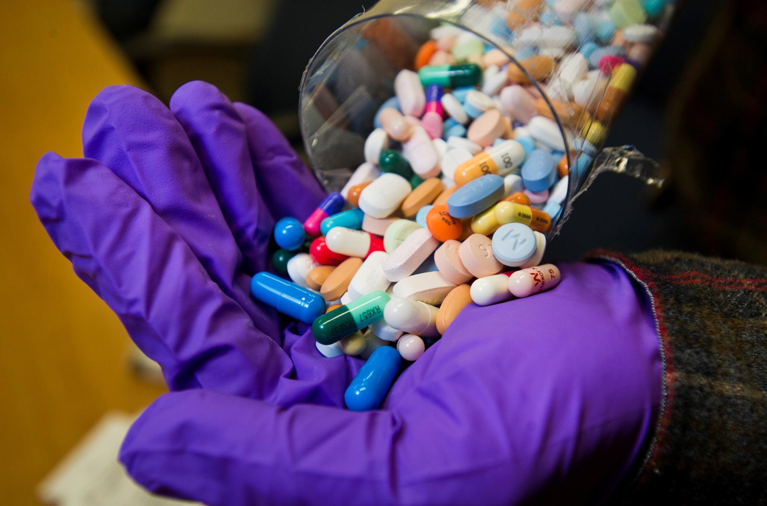A police detective empties a vial of prescription drugs, mostly painkillers, at the station in Columbus, Ind.