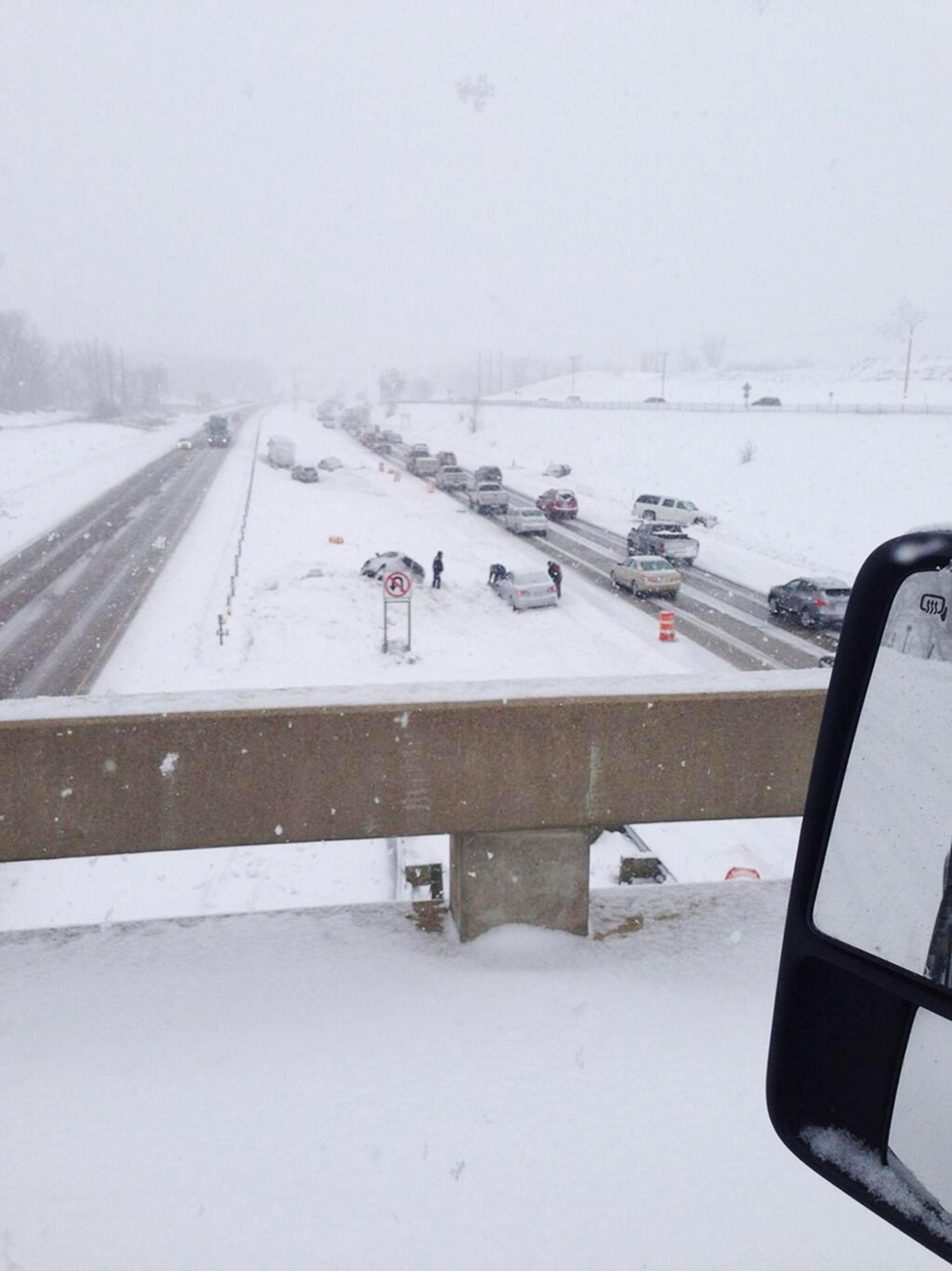 Image: Cars along a snowy highway after multiple crashes caused a lane closure on a Minnesota highway