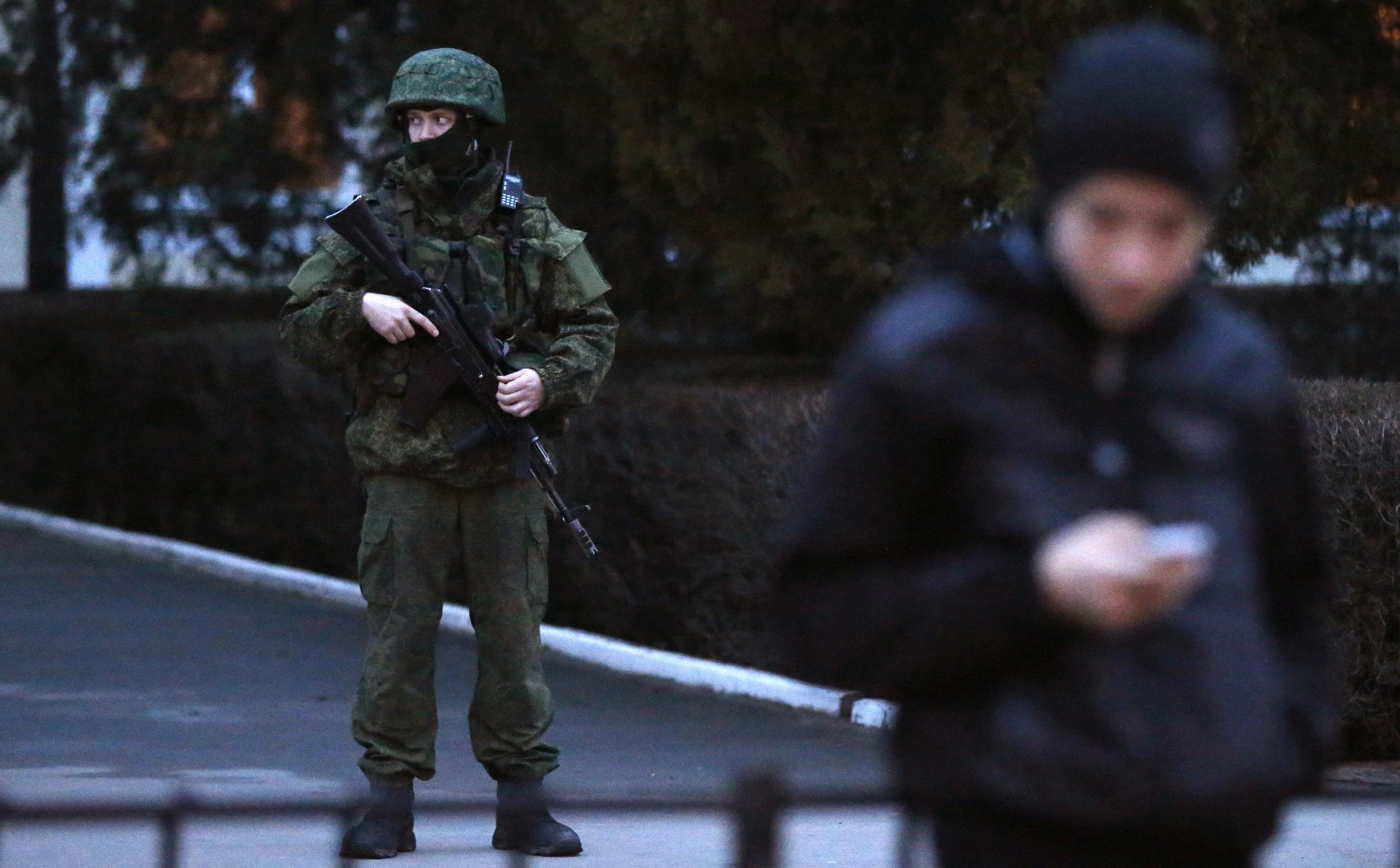 Image: An armed man stands guard at the airport in Simferopol