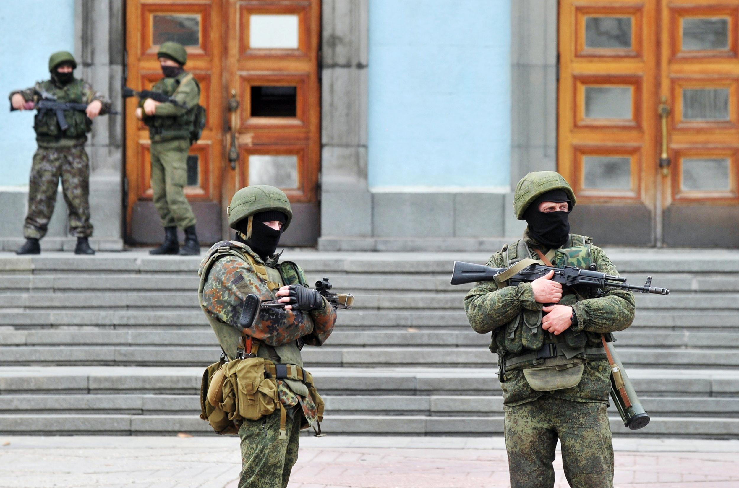Image: Unidentified armed and uniformed men guard the Crimean Cabinet of Ministers building in Simferopol