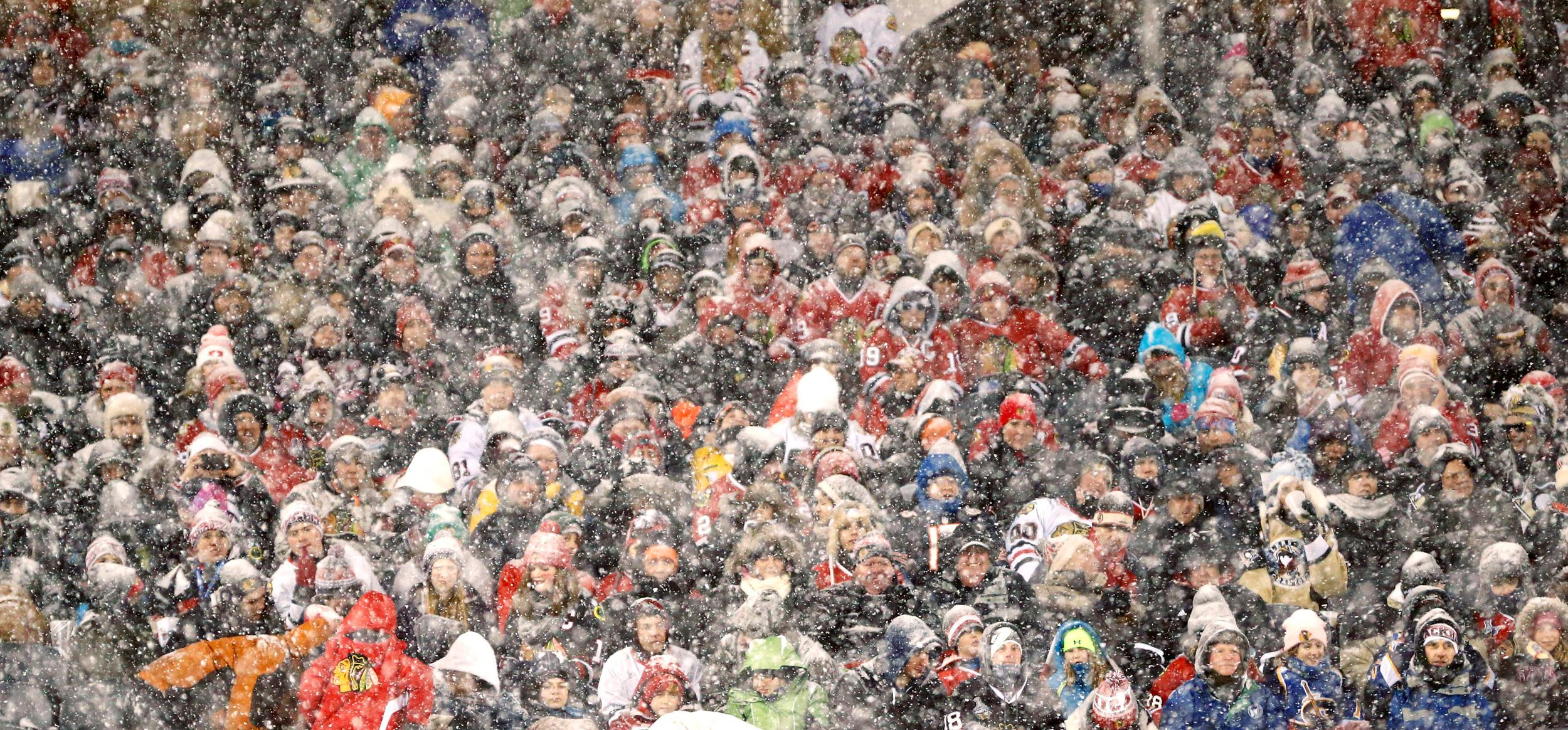 Image: Hockey fans watch the Chicago Blackhawks face the Pittsburgh Penguins as snow falls