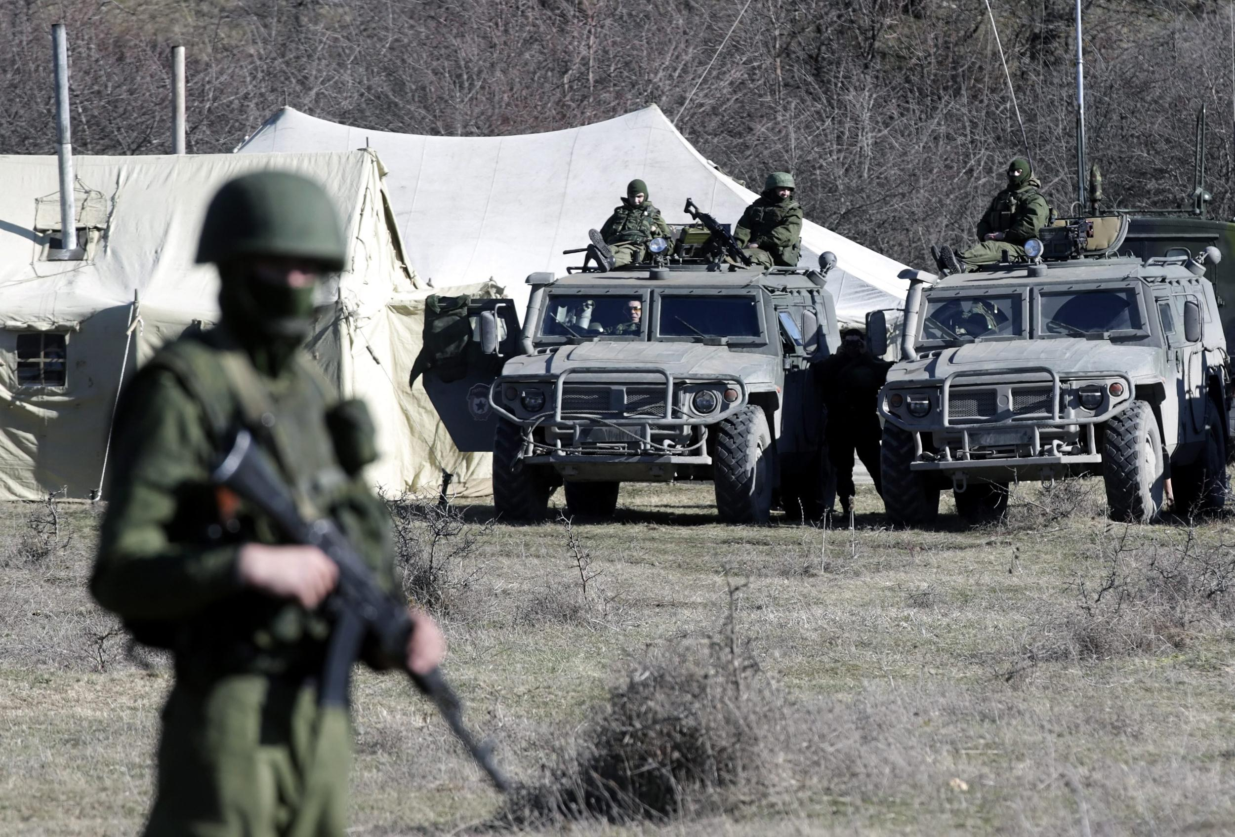 Image: An armed men in military uniform, believed to be Russian, and military vehicles stand outside the territory of a Ukrainian military unit in the village of Perevalnoye