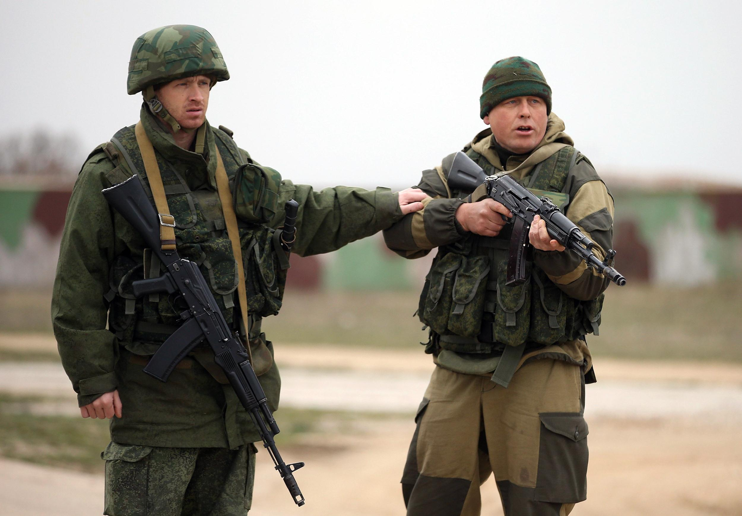 Image: A soldier under Russian command restrains a colleague after he fired his weapon into the air