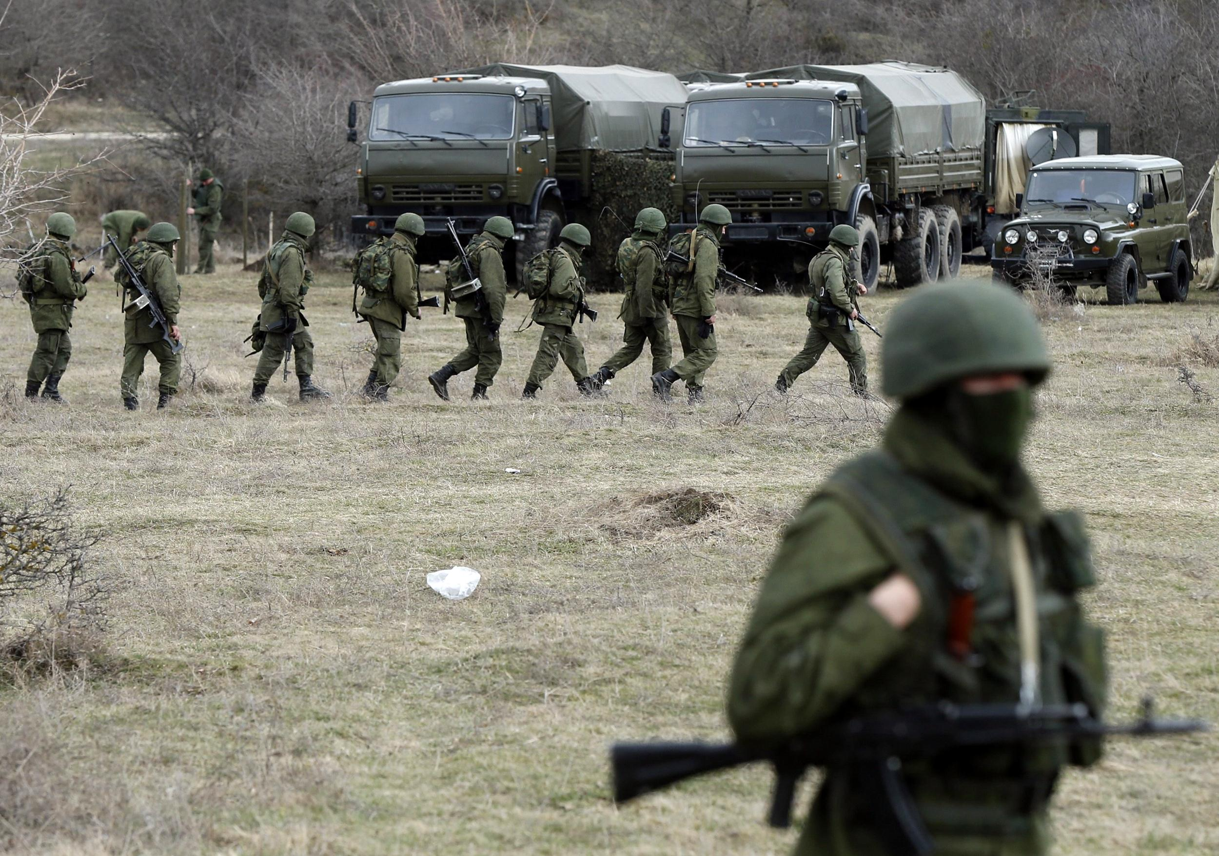 Image: Military personnel, believed to be Russian servicemen, march outside the territory of a Ukrainian military unit in the village of Perevalnoye outside Simferopol