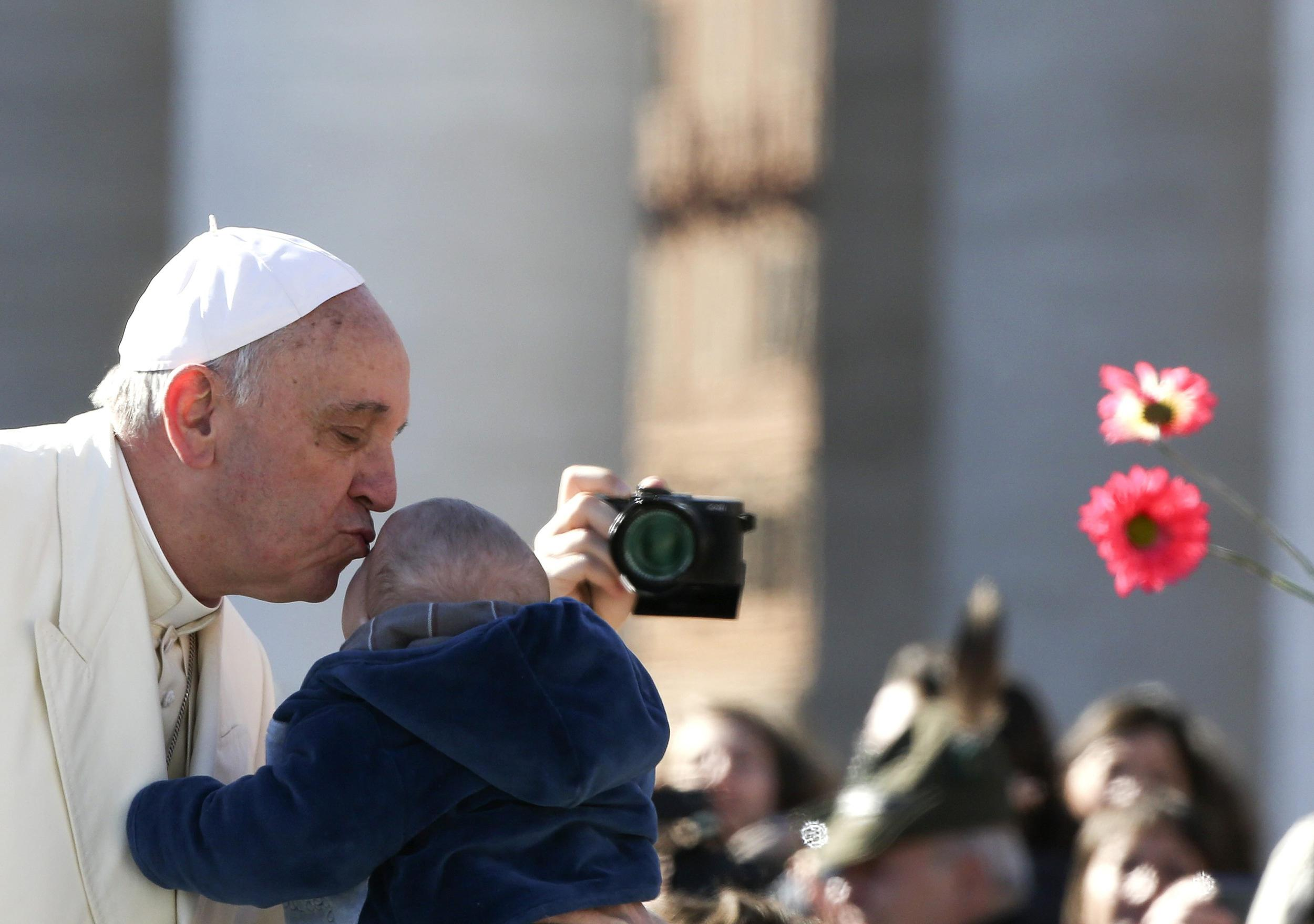 Image: Pope Francis kisses a child as he arrives to lead the general audience in Saint Peter's Square at the Vatican