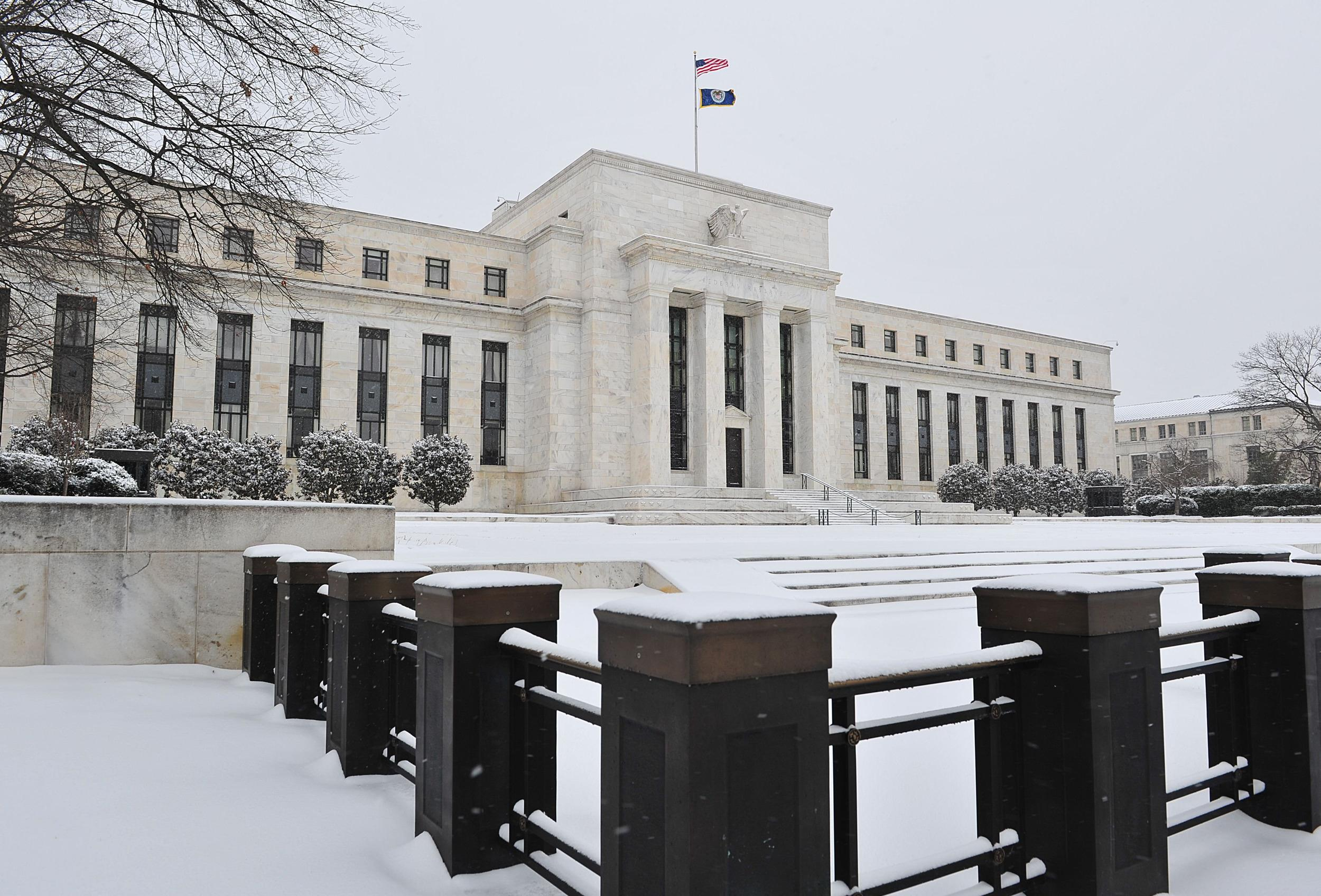 The Federal Reserve is seen during a snow storm. Severe winter weather hit economic activity in January and early February, the central bank said.