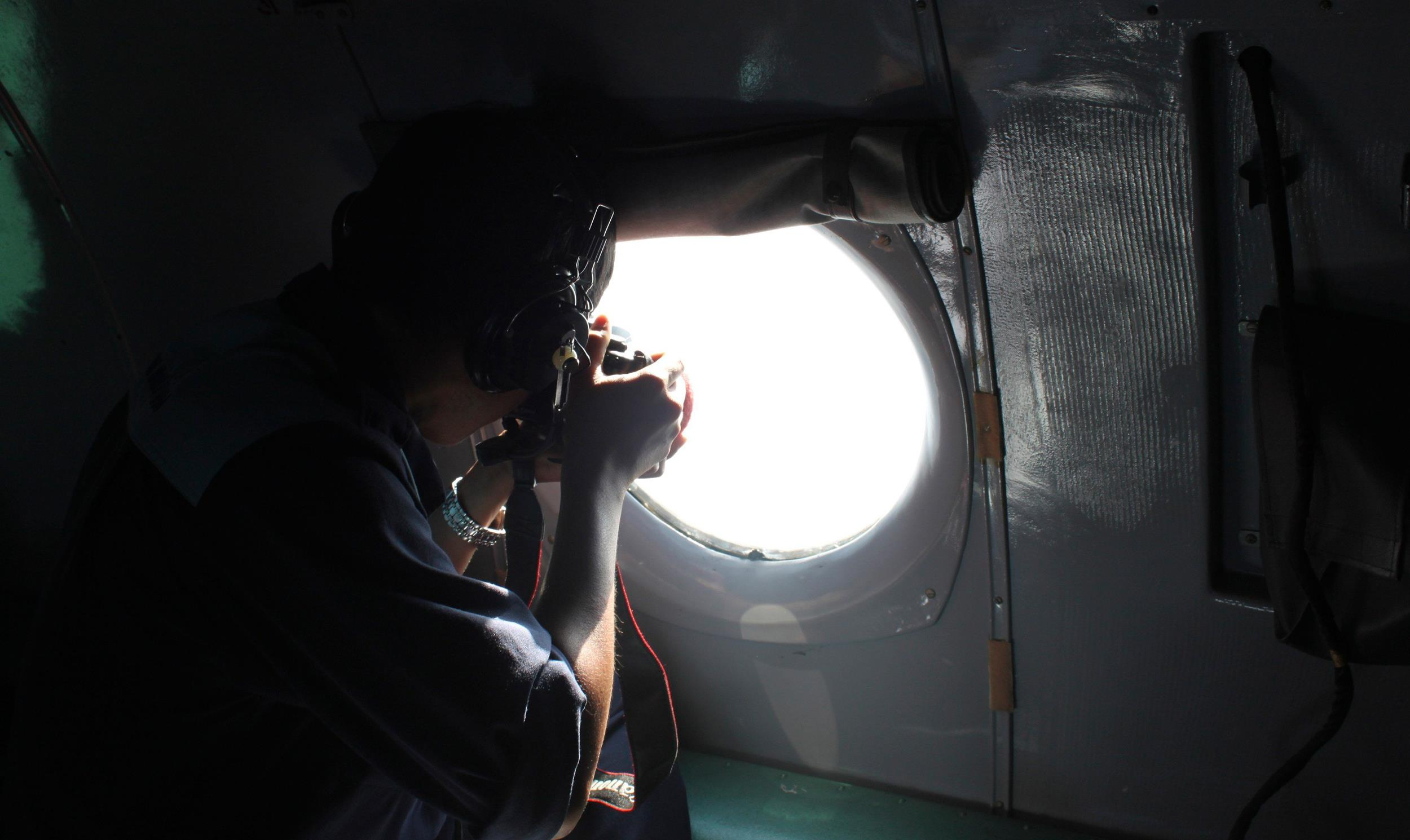 Image: A Vietnamese Air Force officer takes photos from a search and rescue aircraft in the search area for a missing Malaysia Airlines plane