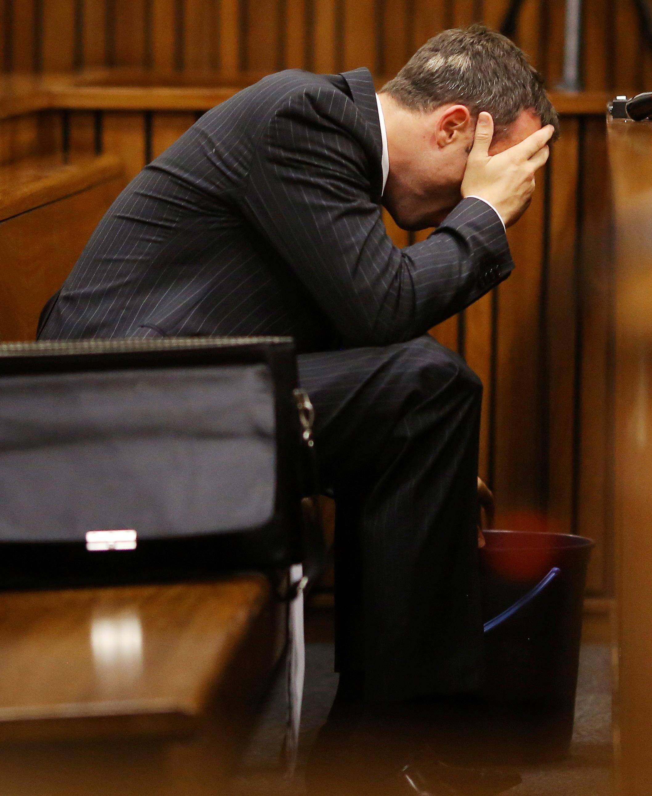 Image: Olympic and Paralympic track star Oscar Pistorius reacts as he reaches for a bucket in the dock during his trial for the murder of his girlfriend Reeva Steenkamp, at the North Gauteng High Court in Pretoria