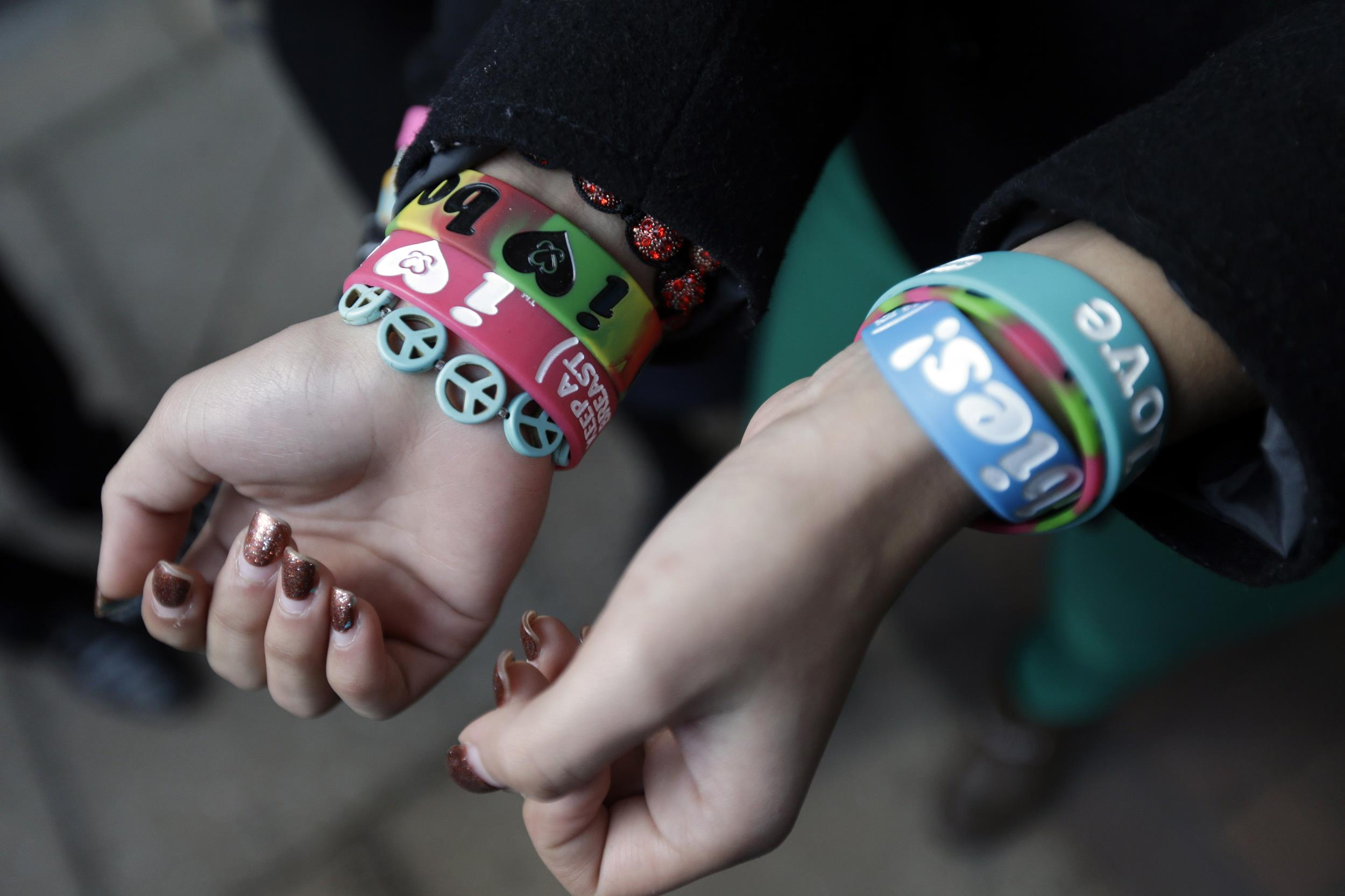 Image: Brianna Hawk, 15, left, and Kayla Martinez, 14, display their bracelets for photographers