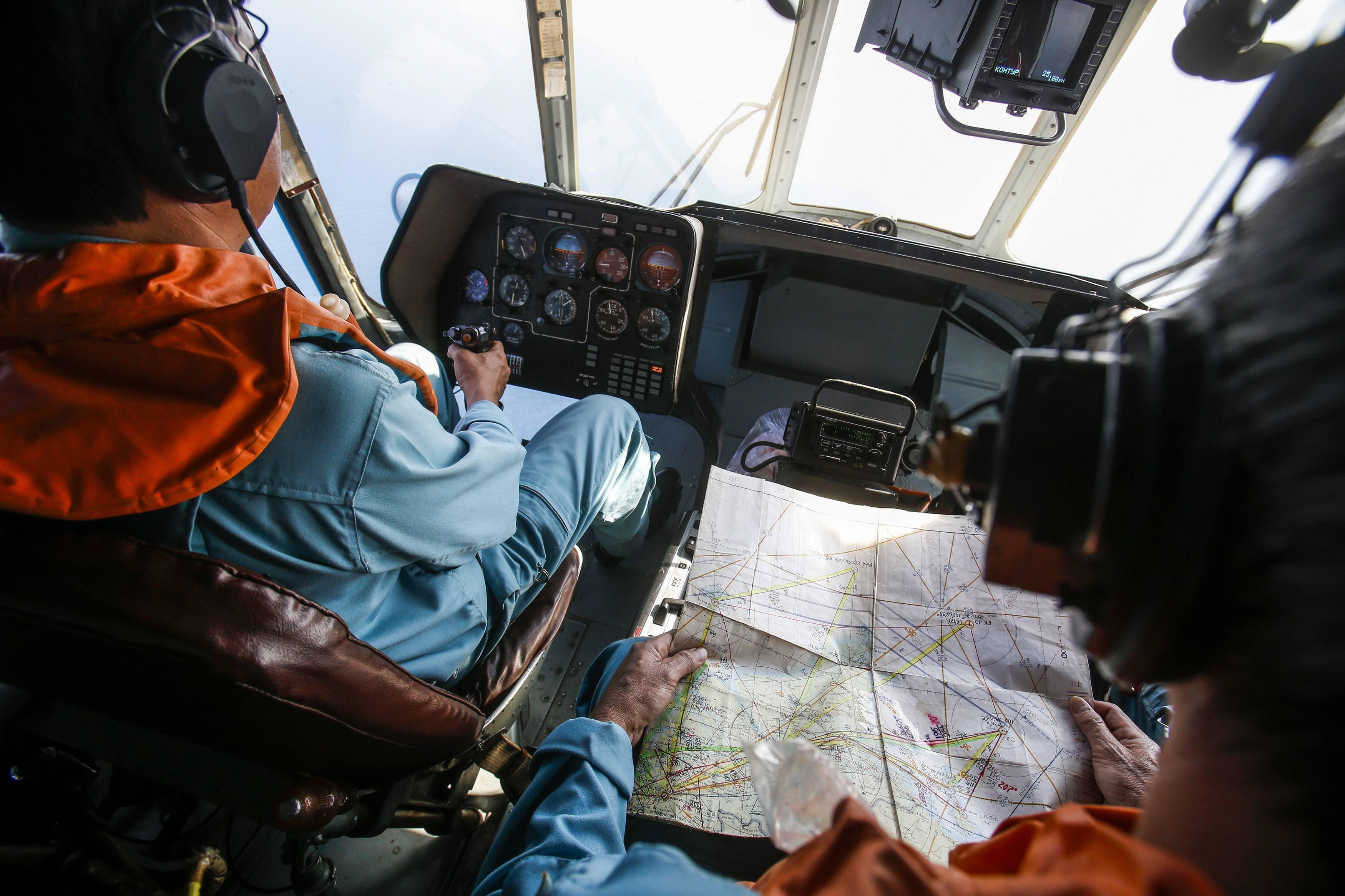 Image: Military personnel work in cockpit of helicopter belonging to Vietnam Air Force during mission to find Malaysia Airlines flight MH370, near Tho Chu island