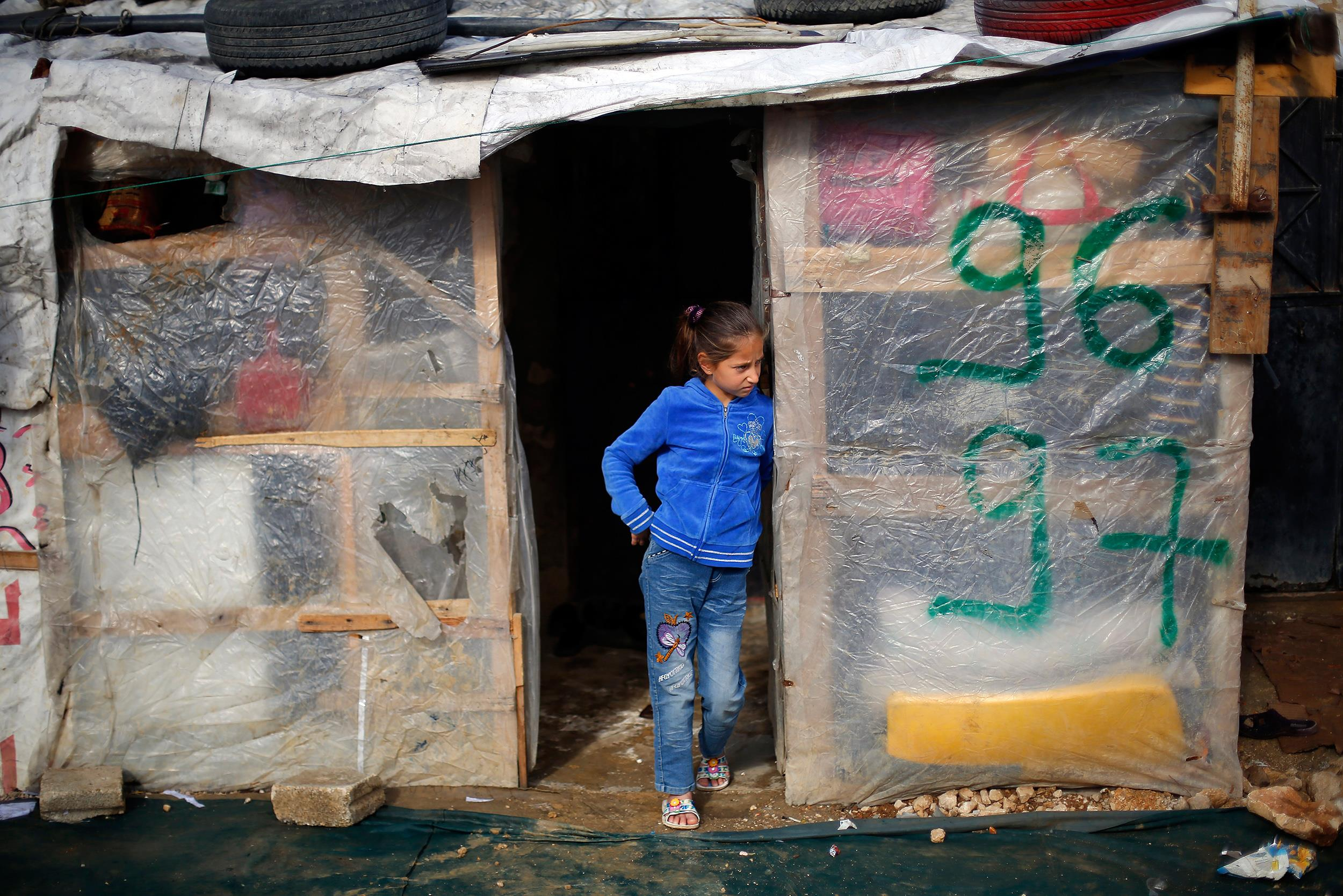 Image:A Syrian refugee child stands outside her shack in the Fayda Camp, some 25 miles east of Beirut