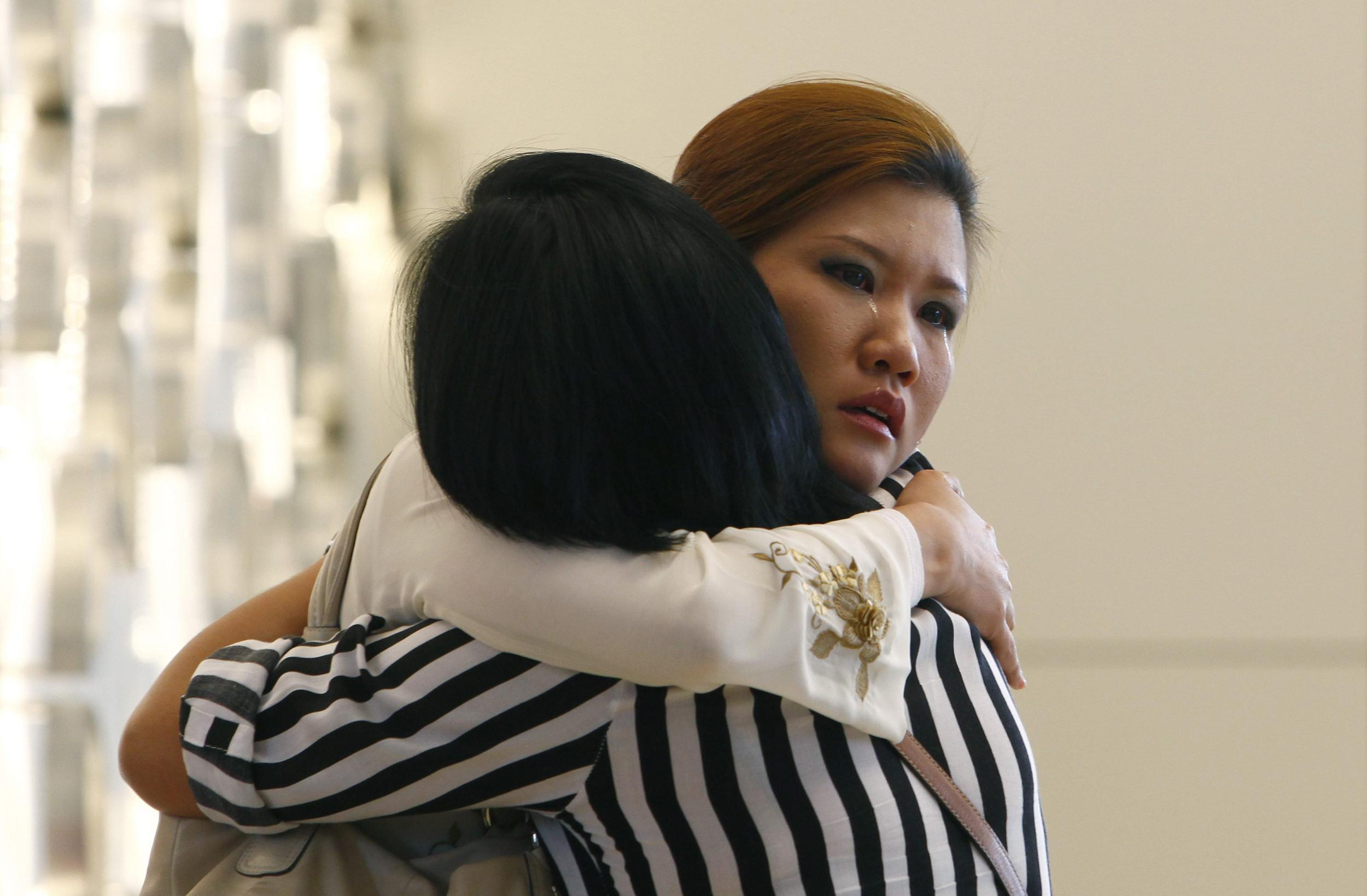 Image: Relatives of a passenger onboard the missing Malaysia Airlines flight MH370 cry inside a hotel they are staying, in Putrajaya