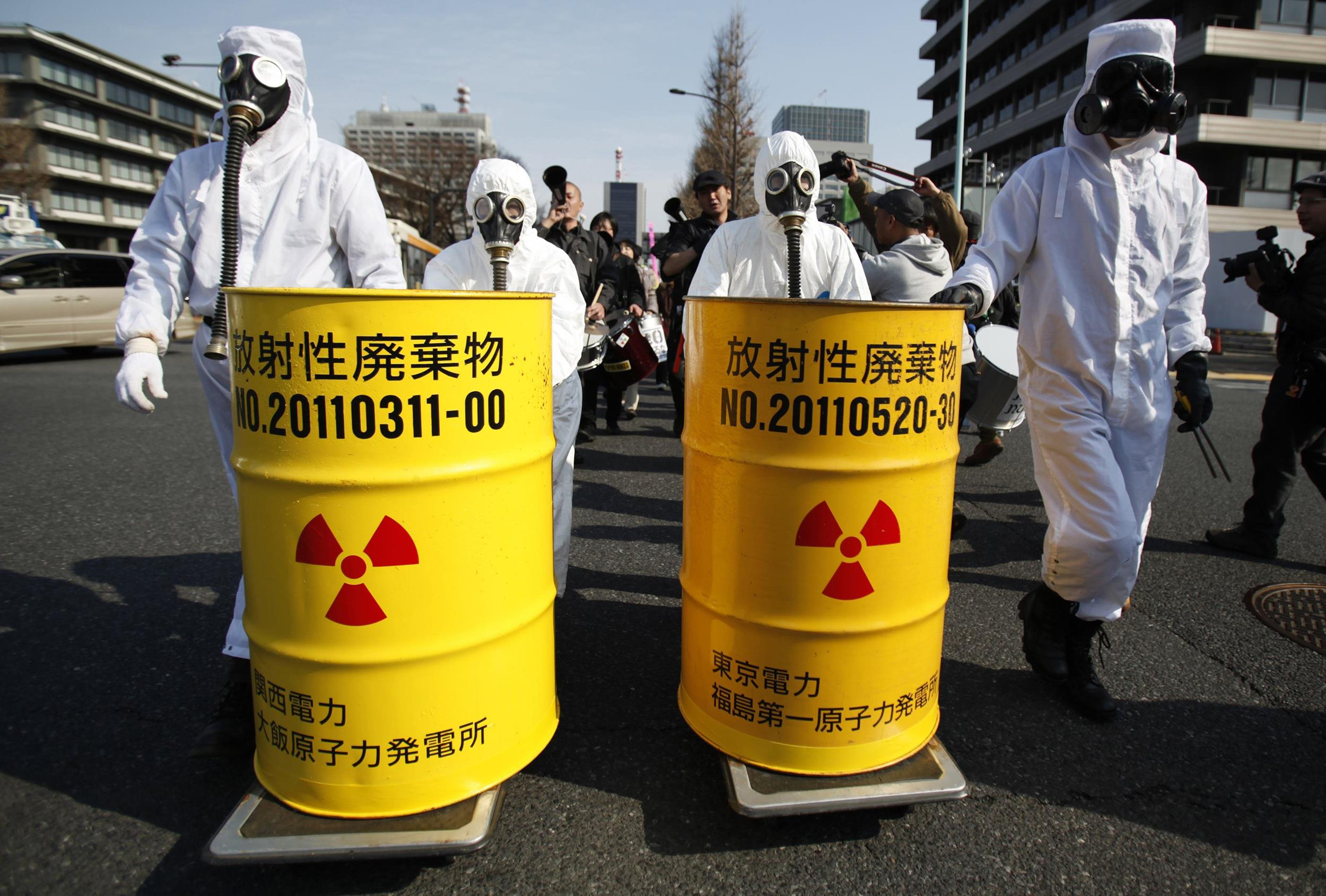 Image: Anti-nuclear protesters wearing protective suits push mock drums which are labeled as radioactive waste from Kansai Electric Power Co's Ohi nuclear power plant and TEPCO's Fukushima nuclear power plant as they march in Tokyo