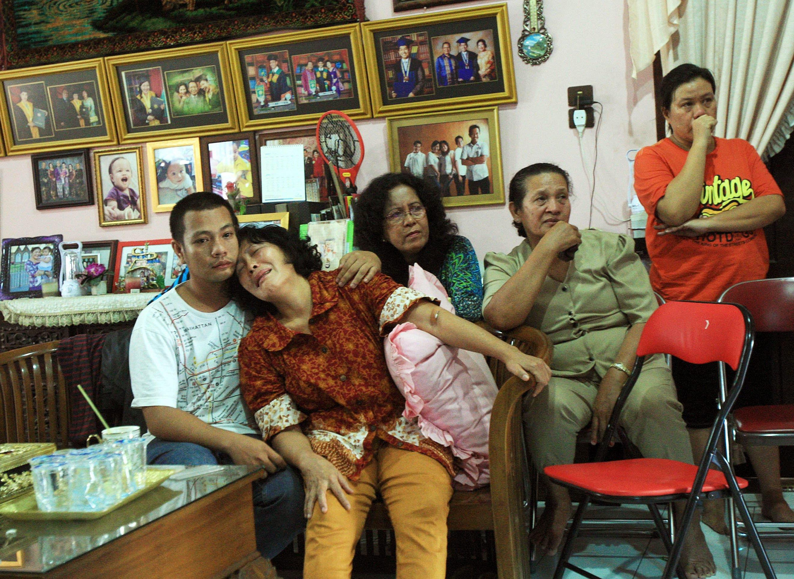 Image: Indonesian family of Firman Chandra Siregar cry as they watch television at their house in Medan
