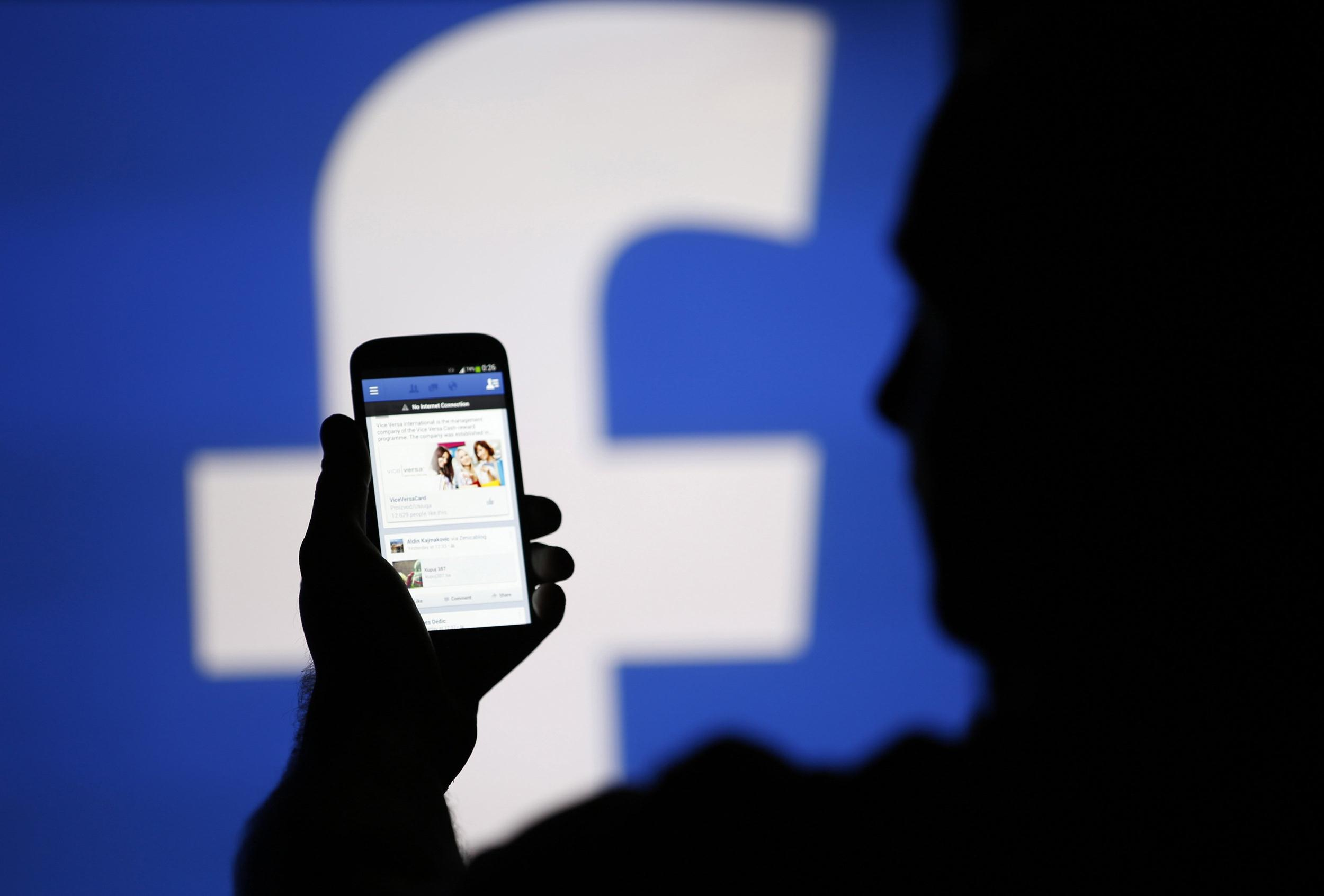 Image: A man is silhouetted against a video screen with an Facebook logo as he poses with an Samsung S4 smartphone in this photo illustration taken in the central Bosnian town of Zenica