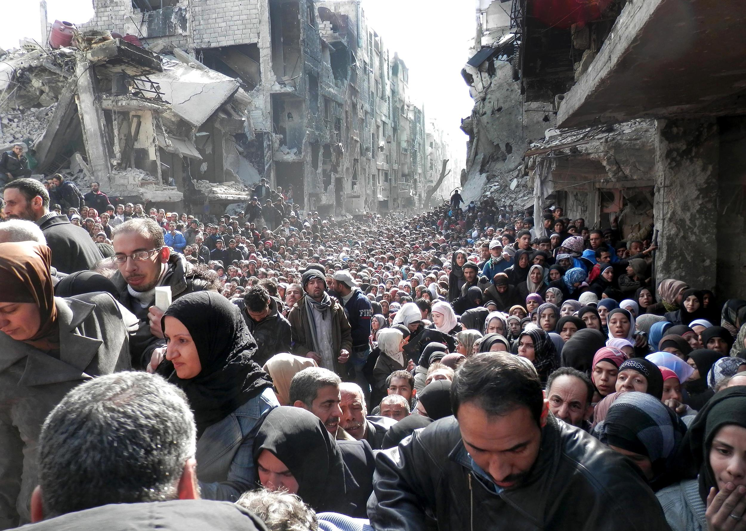 Image: Residents of the besieged Palestinian camp of Yarmouk queuing to receive food supplies in Damascus.