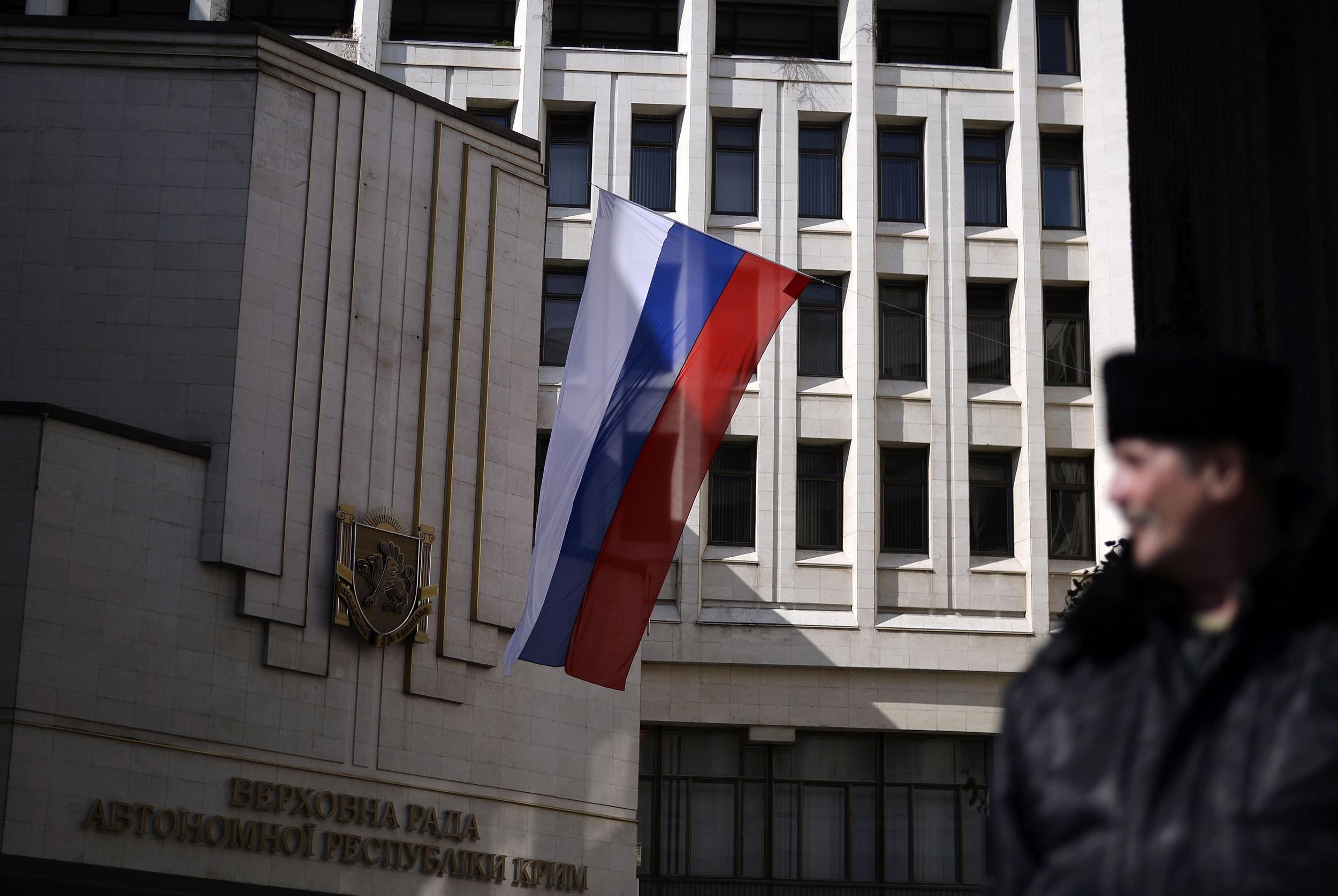 Image: A pro-Russian Cossack man stands guard in front of Crimea's regional parliament building