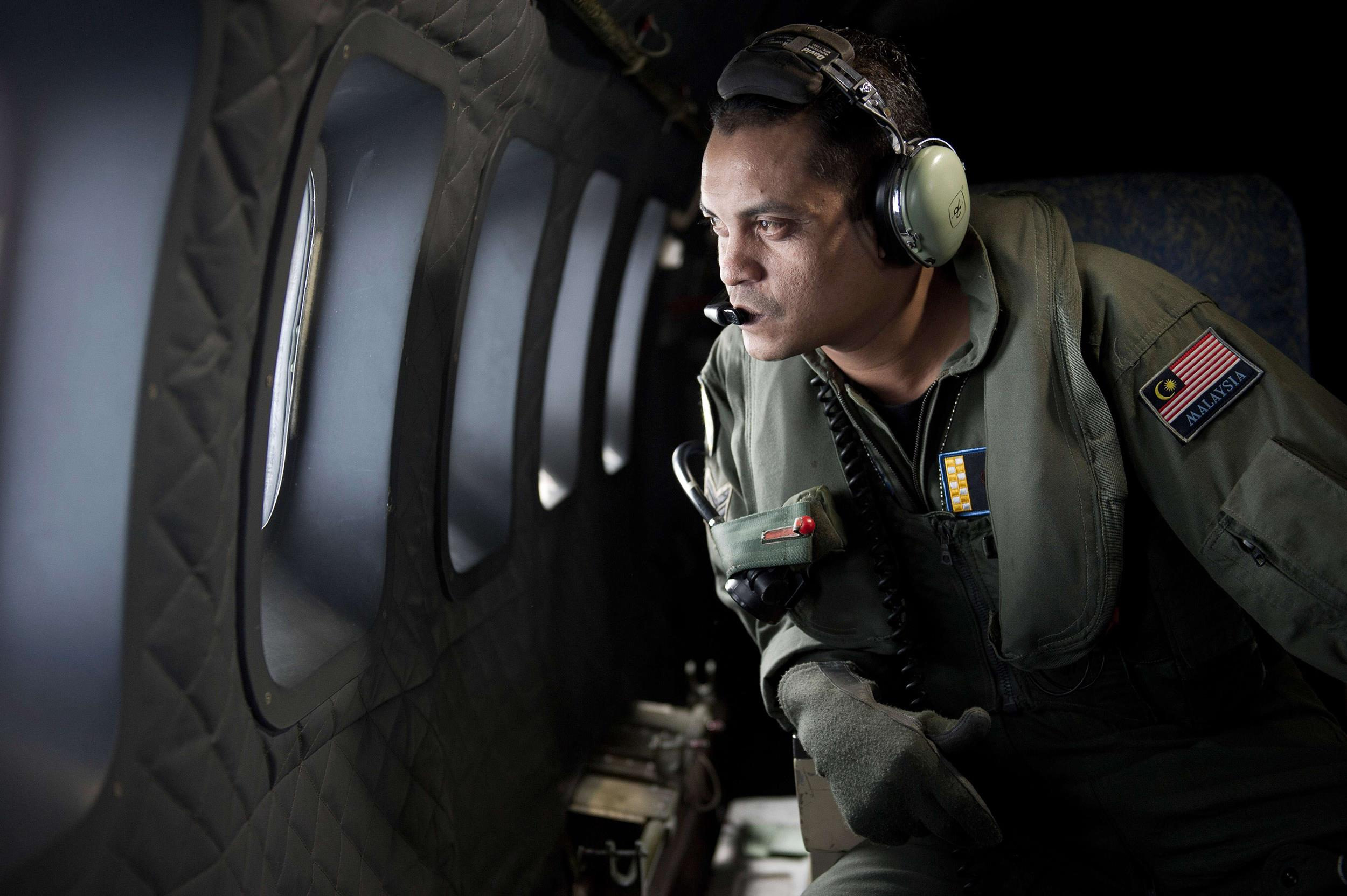 Image: A crew member looks out the windows from a Malaysian Air Force CN235 aircraft during a search and rescue operation