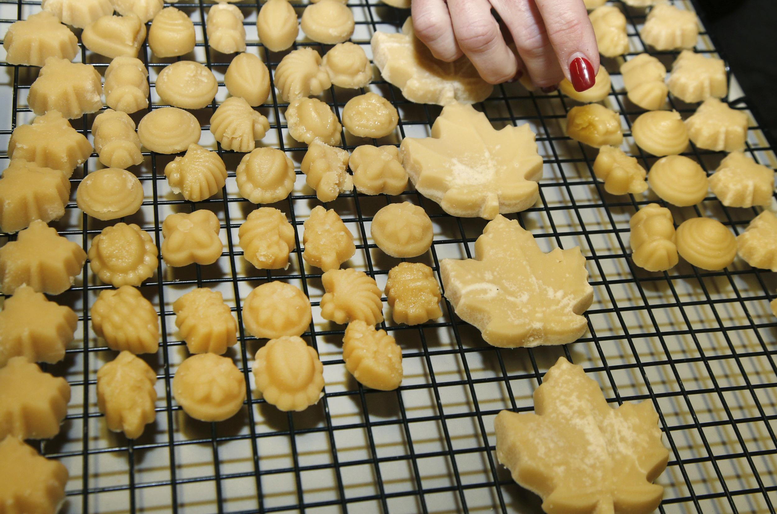 Image: Kathy Gallagher places maple sugar candy on a drying rack at the Turtle Lane Maple sugar house in North Andover, M