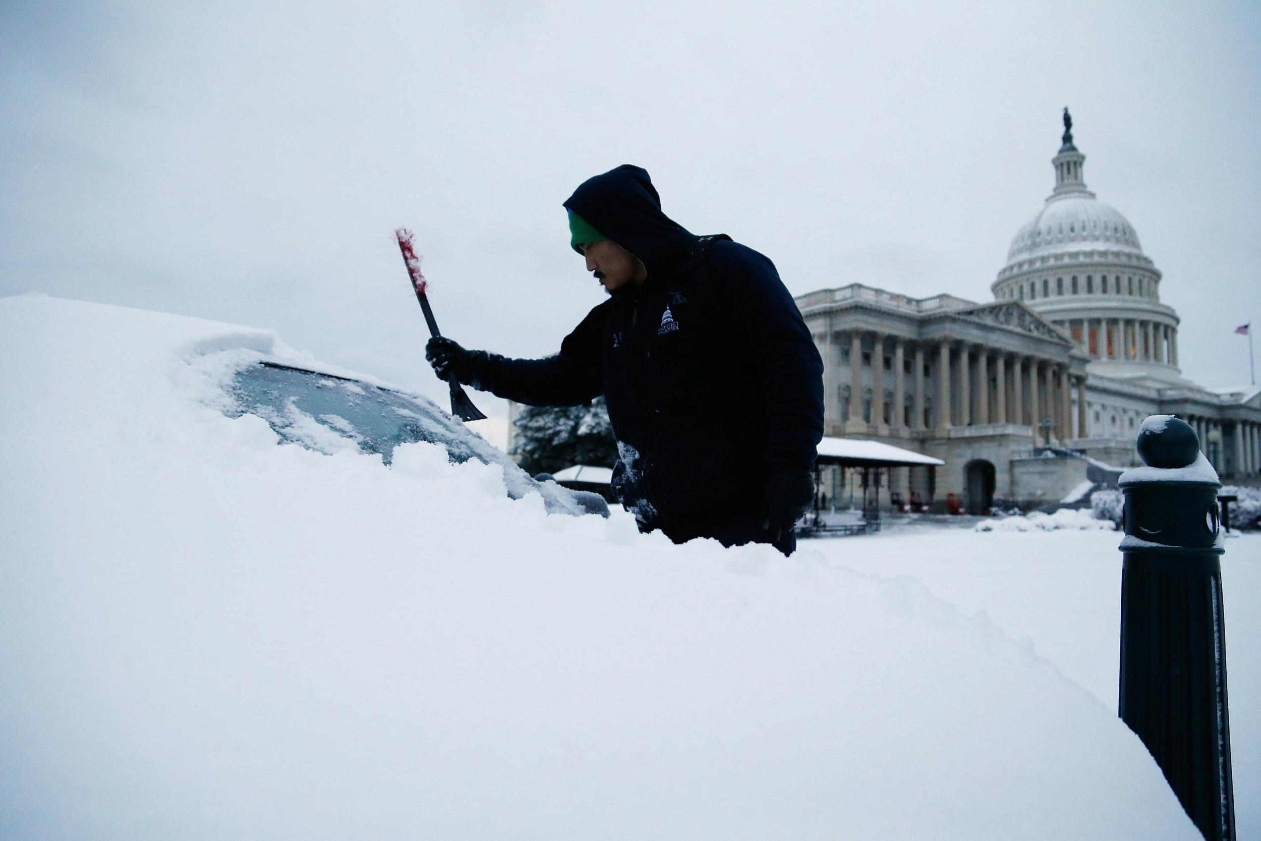 Image: After finishing an overnight shift, a worker clears the snow from his car at the U.S. Capitol in Washington