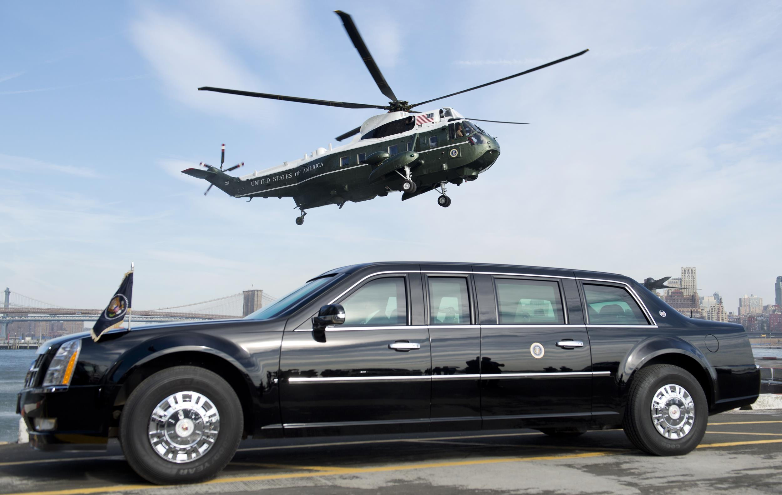Image: Marine One helicopter, carrying US President Barack Obama, prepares to land next to the Presidential limousine, known as